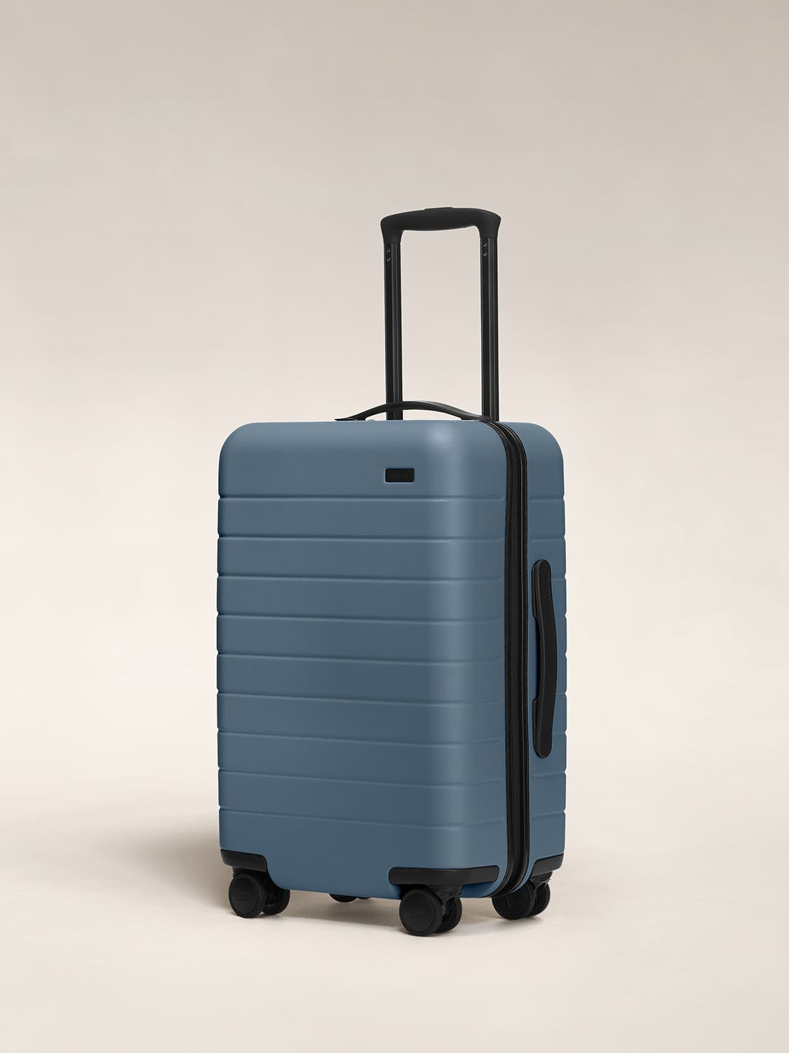 Coast blue carry-on hardside with raised telescopic handles shown at an angle.