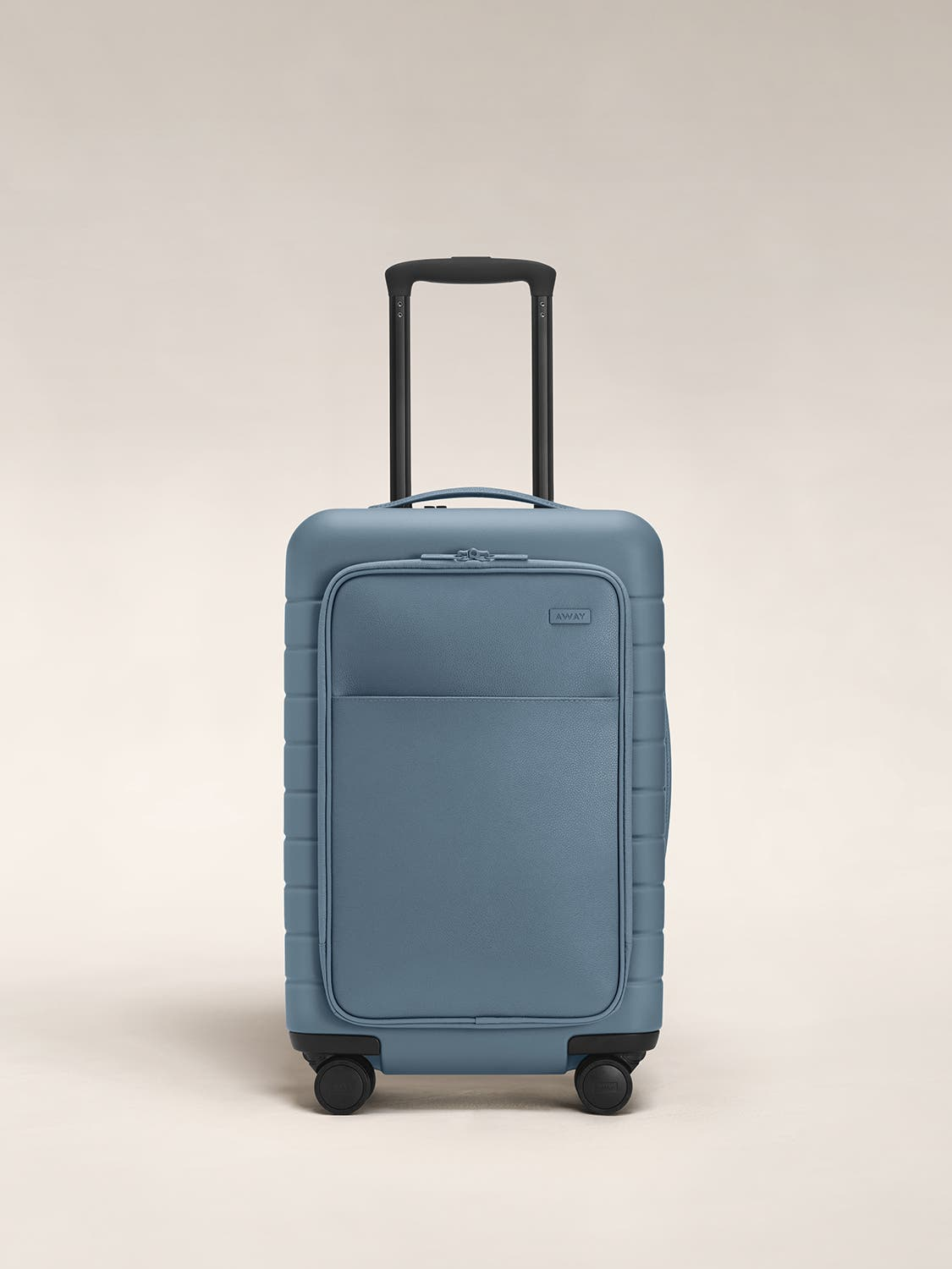 Front view of a coast carry-on suitcase with a hard shell, leather front pocket, and telescopic handle pulled out.