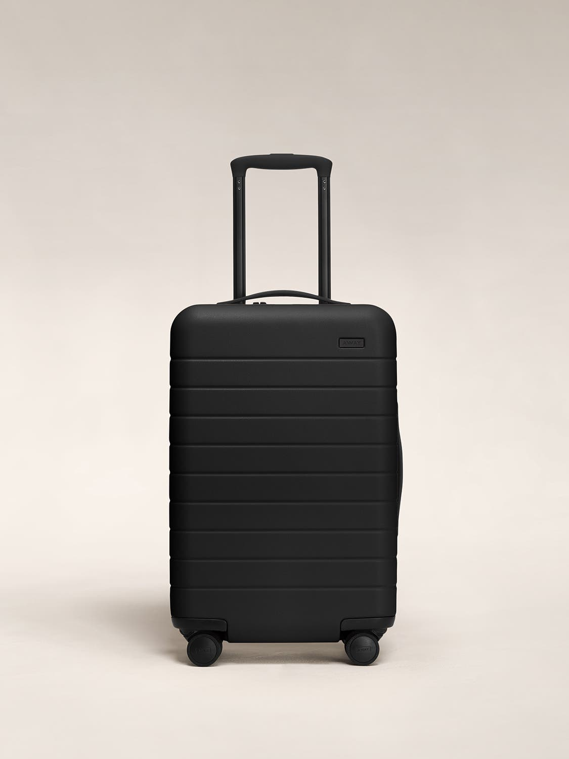 Front view of a black carry-on suitcase with a hard shell, nylon front pocket, and telescopic handle pulled out.