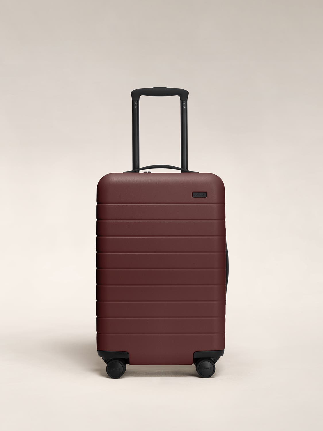 Front view of a brick red carry-on suitcase with a hard shell, nylon front pocket, and telescopic handle pulled out.