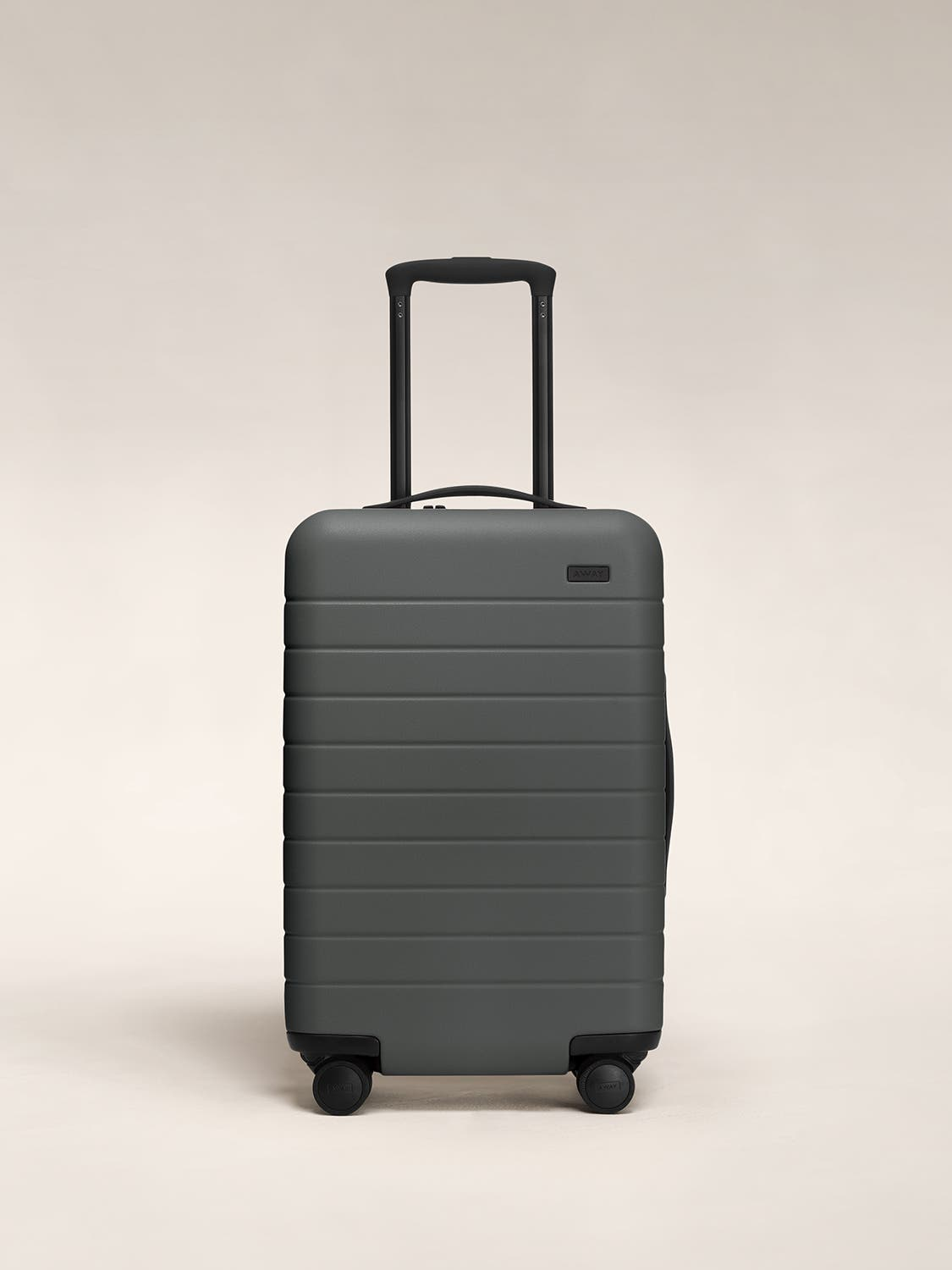 Front view of an asphalt carry-on suitcase with a hard shell, nylon front pocket, and telescopic handle pulled out.