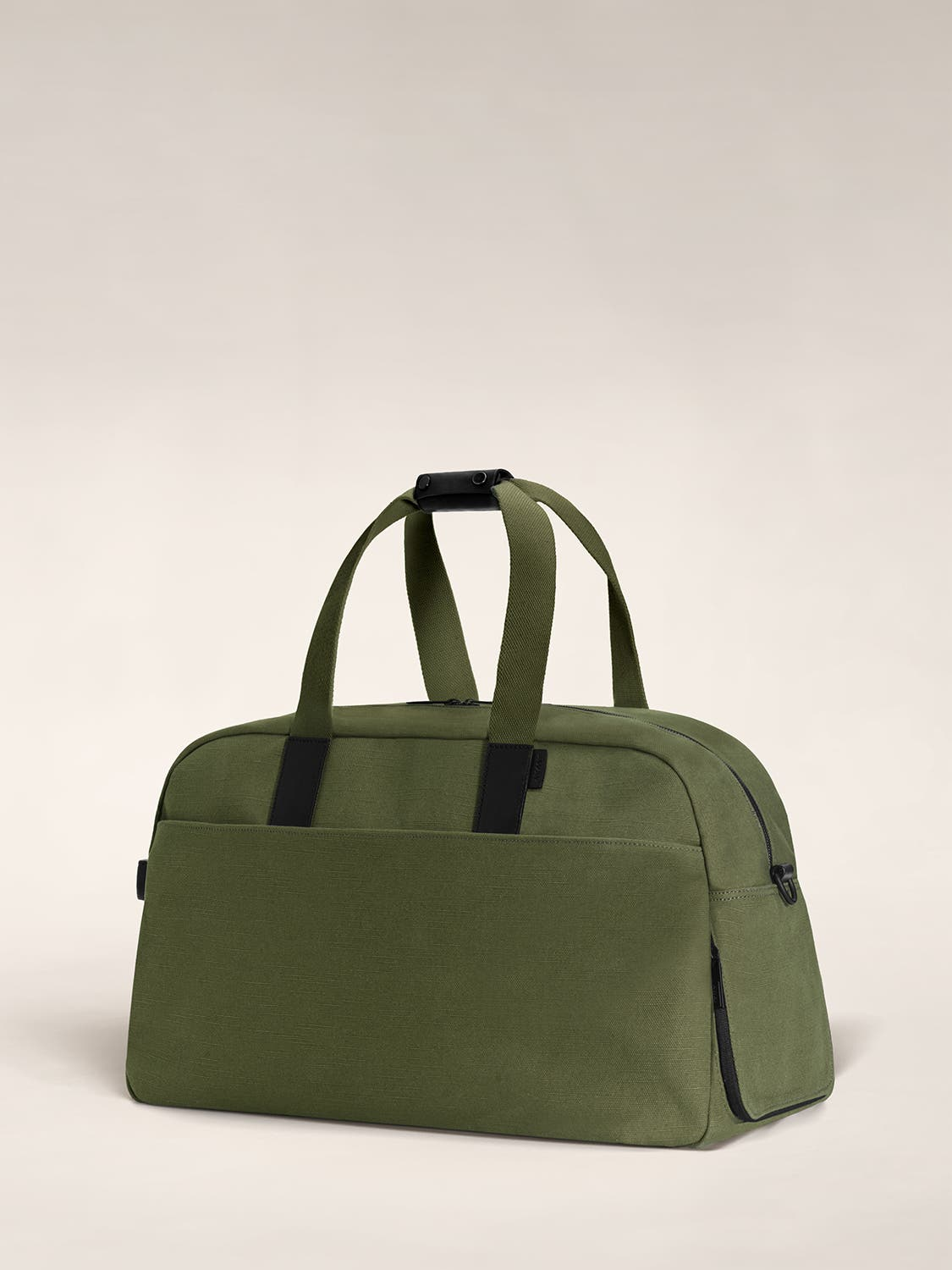 Angled view of a olive color canvas duffle bag with black leather trim.