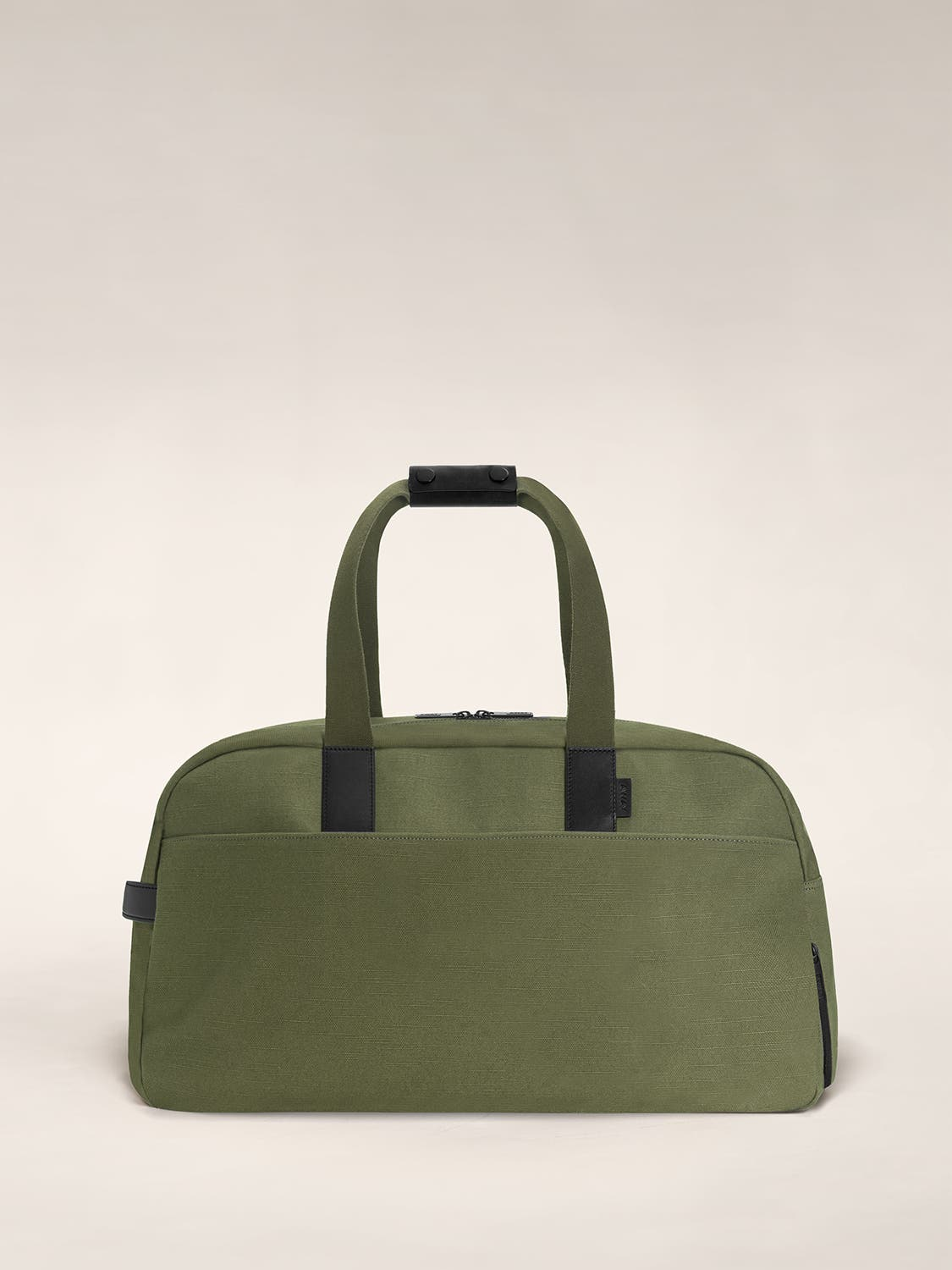 A canvas duffle bag in the color olive with black leather trim.