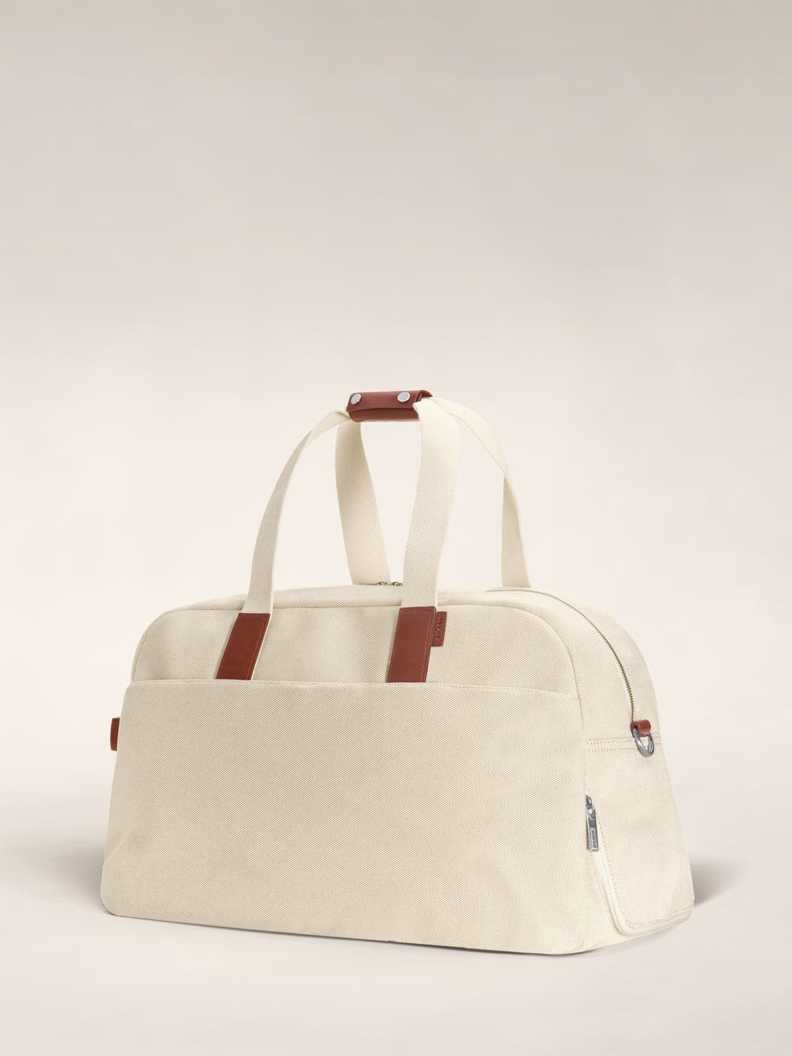 Angled view of a sand color canvas duffle bag with brown leather trim.