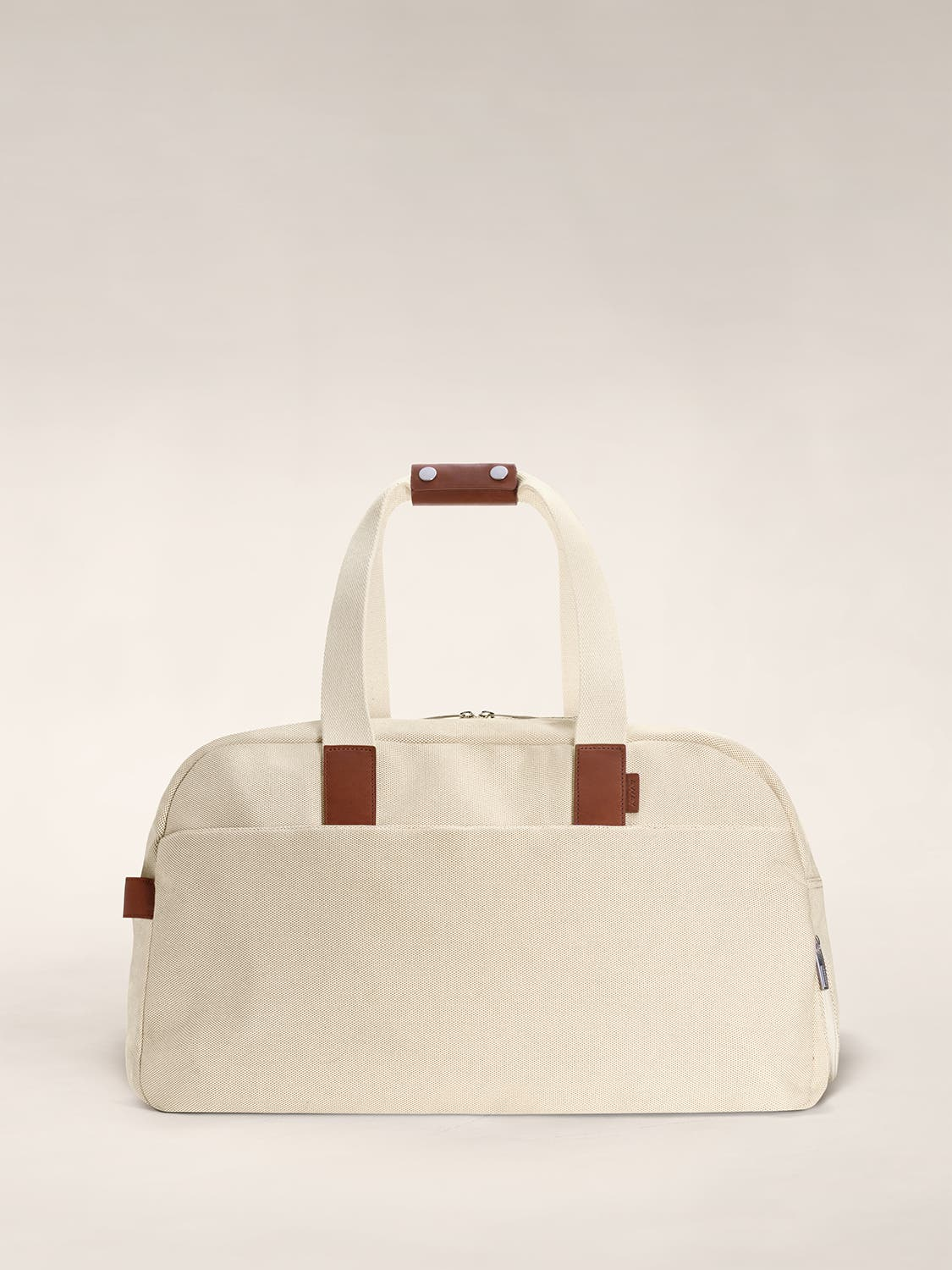A canvas duffle bag in the color sand with brown leather trim.
