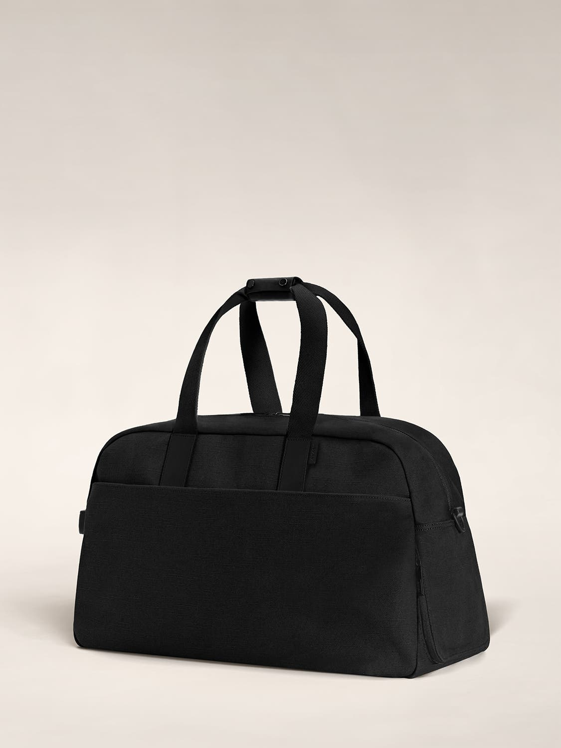 Angled view of a black color canvas duffle bag with black leather trim.