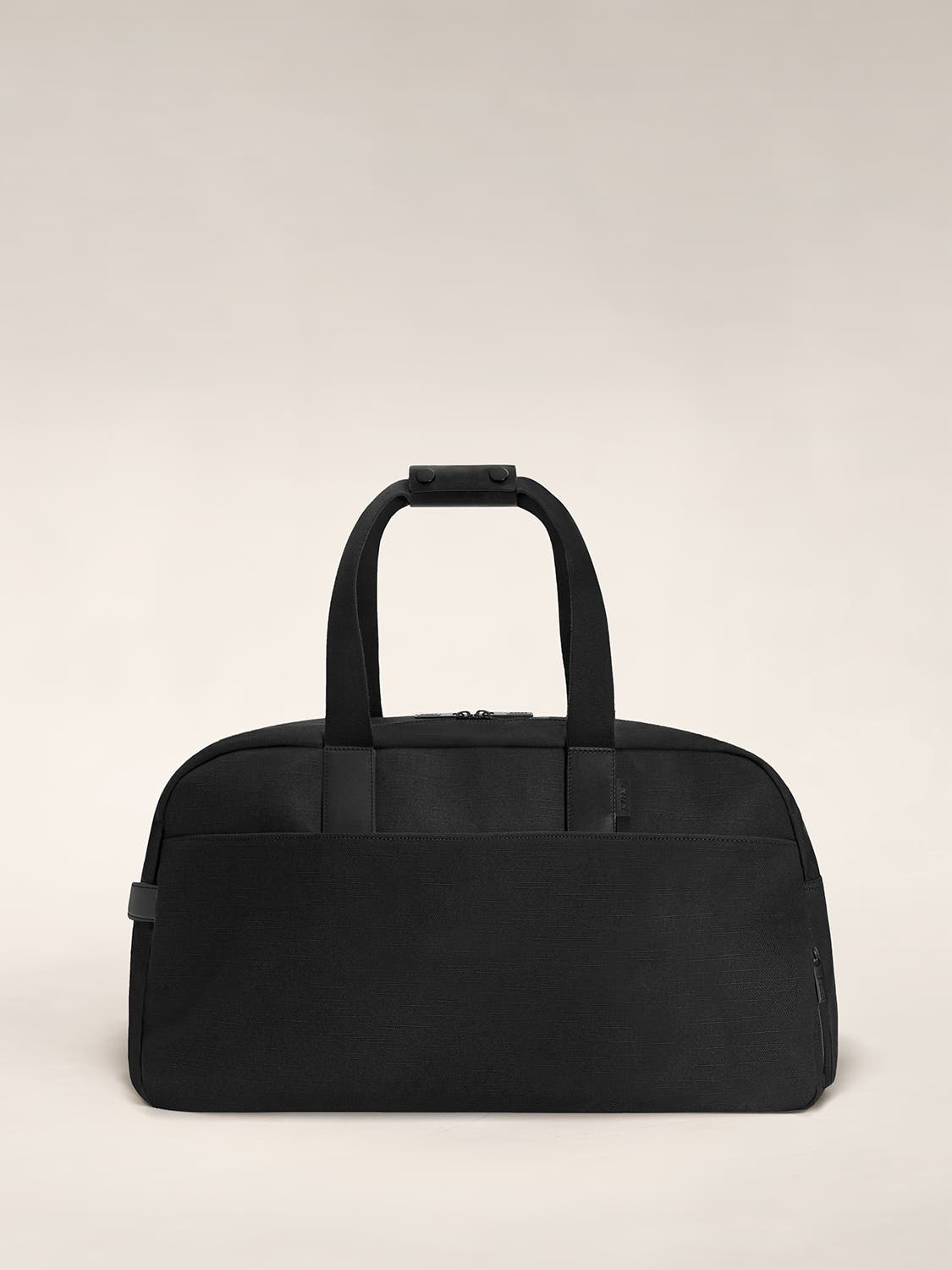 A canvas duffle bag in the color black with black leather trim.