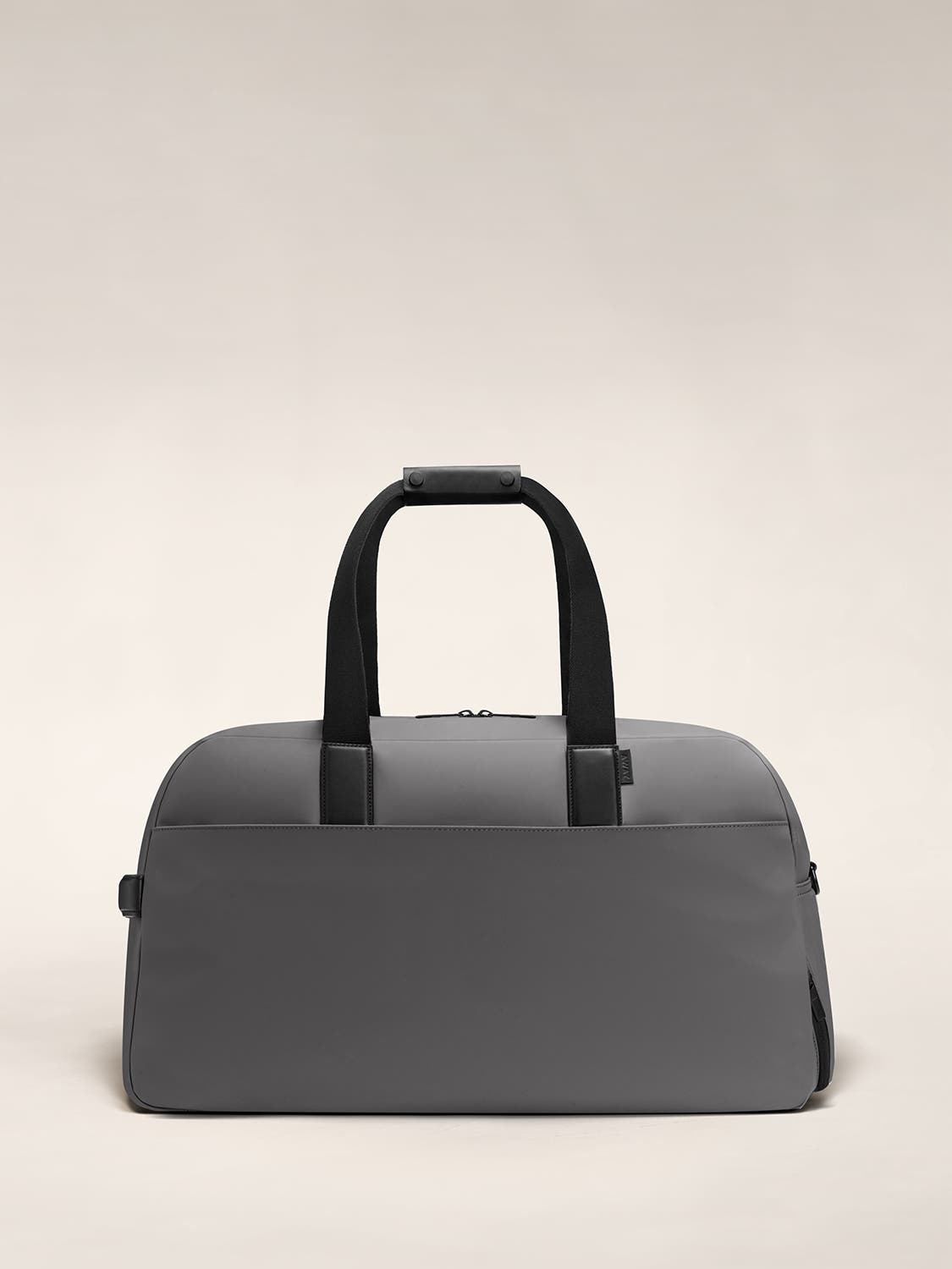 A nylon duffle bag in the color asphalt with black leather trim.