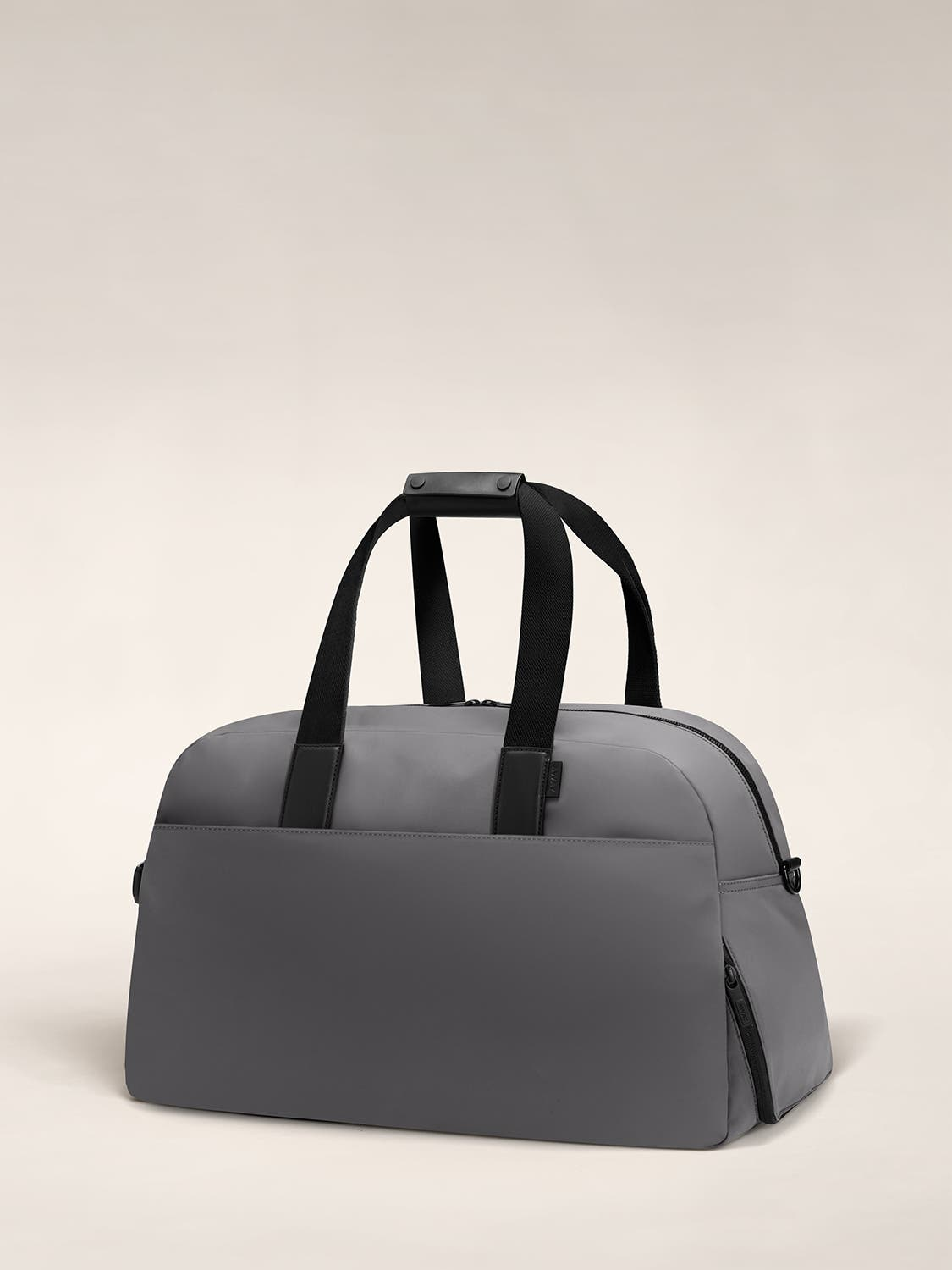 Angled view of an asphalt color nylon duffle bag with black leather trim.