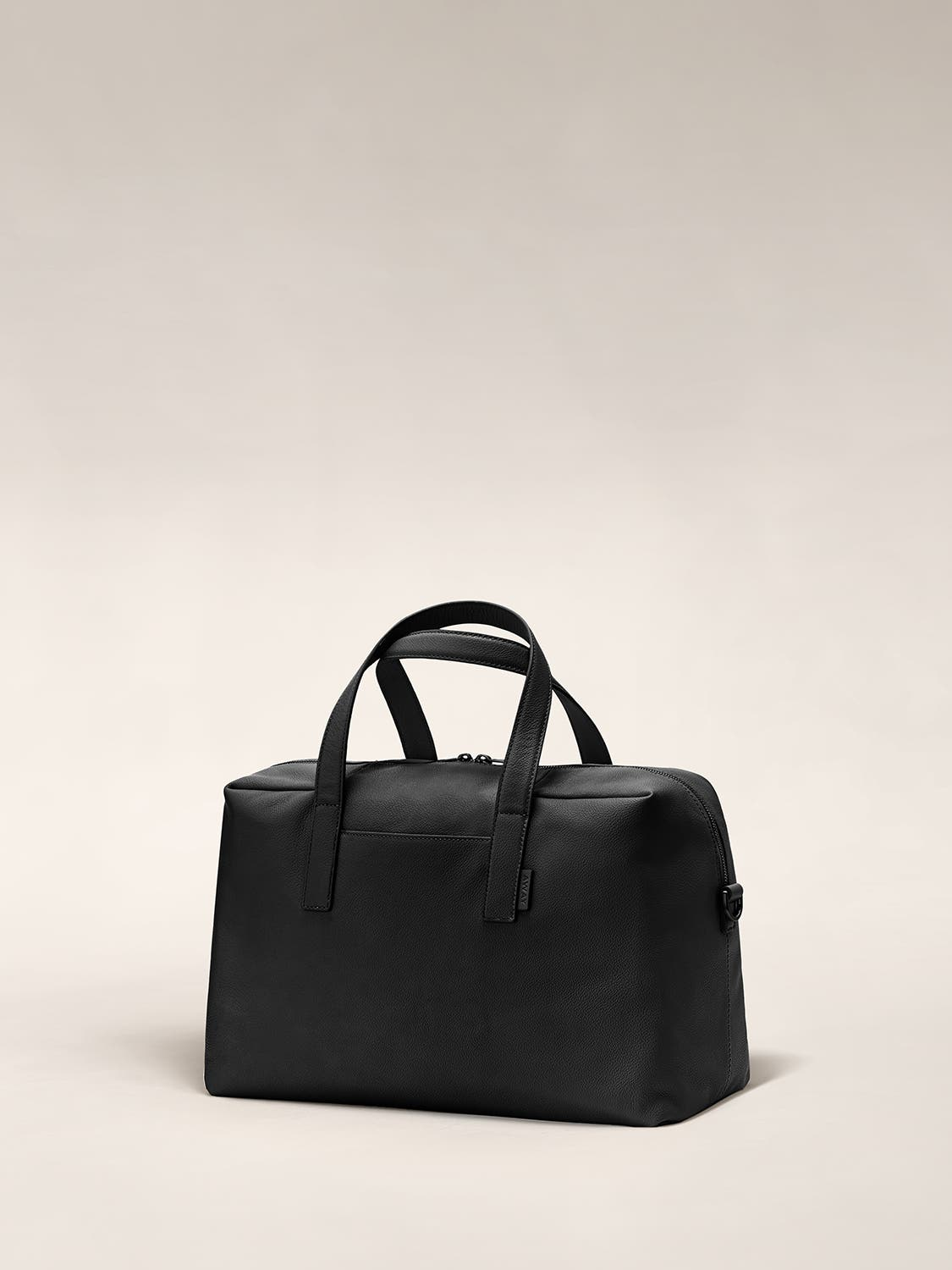 Angled view of a black duffle bag with crossed straps.