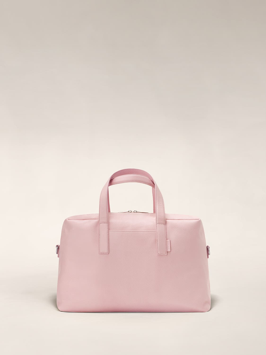 Front of a blush duffle bag with raised straps.