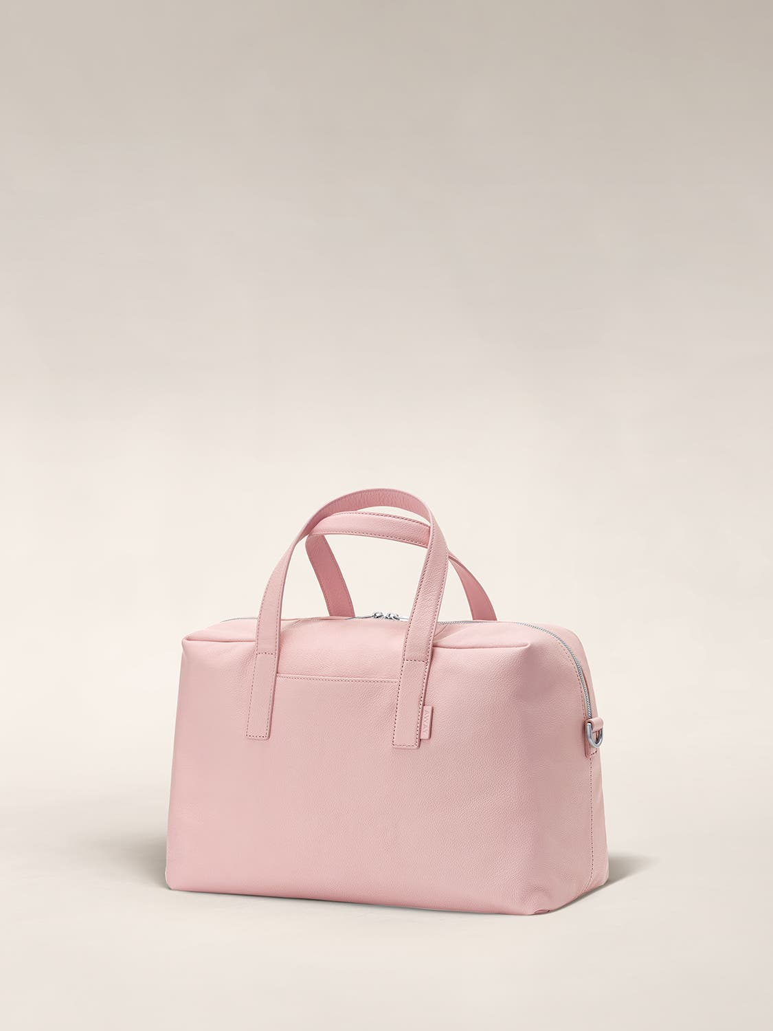 Angled view of a blush duffle bag with crossed straps.