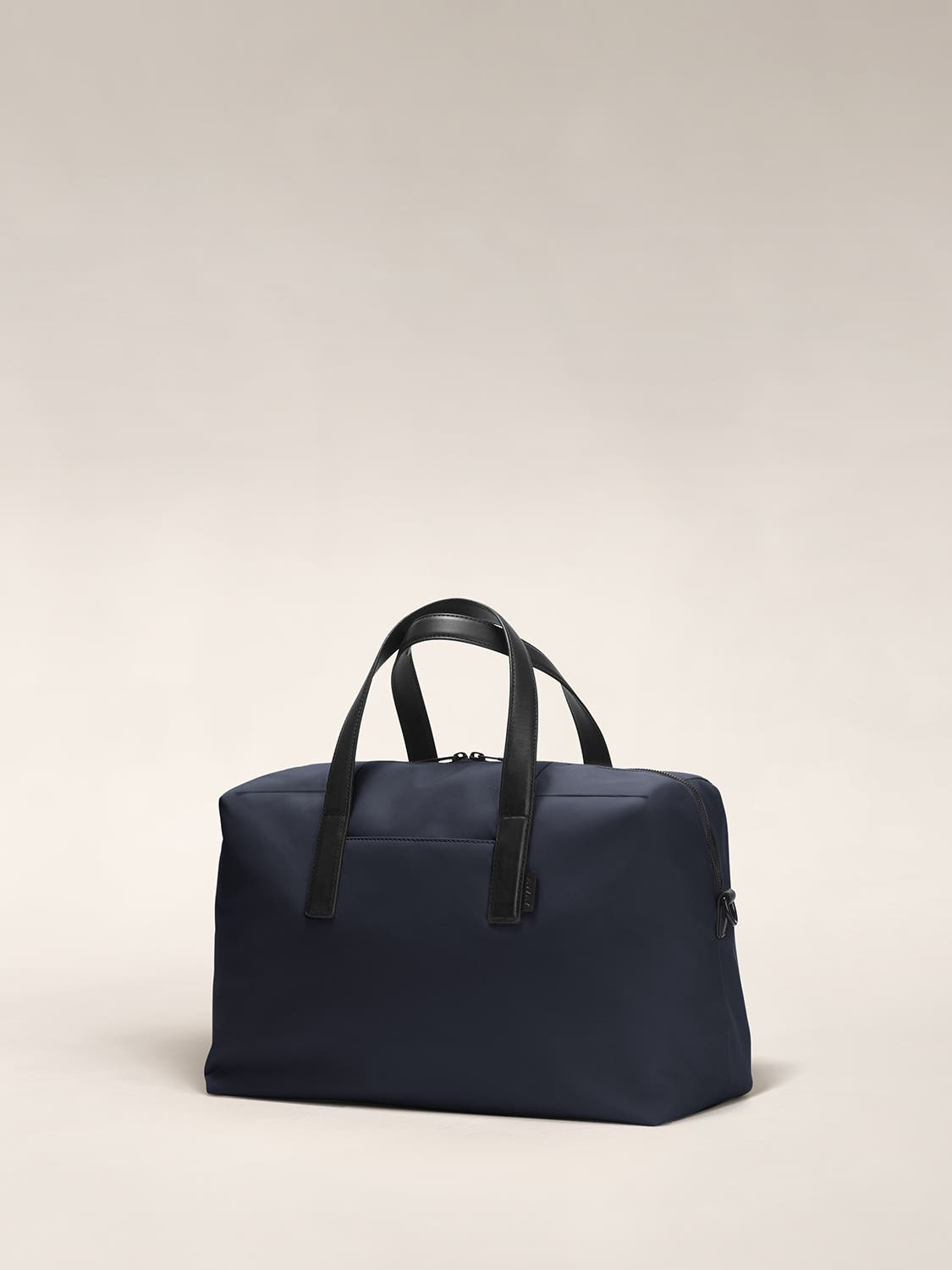 Angled view of a navy duffle bag with crossed straps.