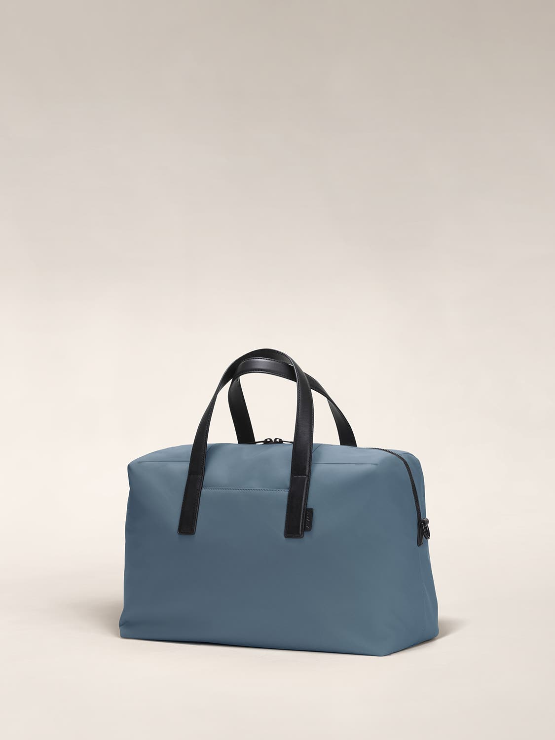 Angled view of a coast blue duffle bag with crossed straps.