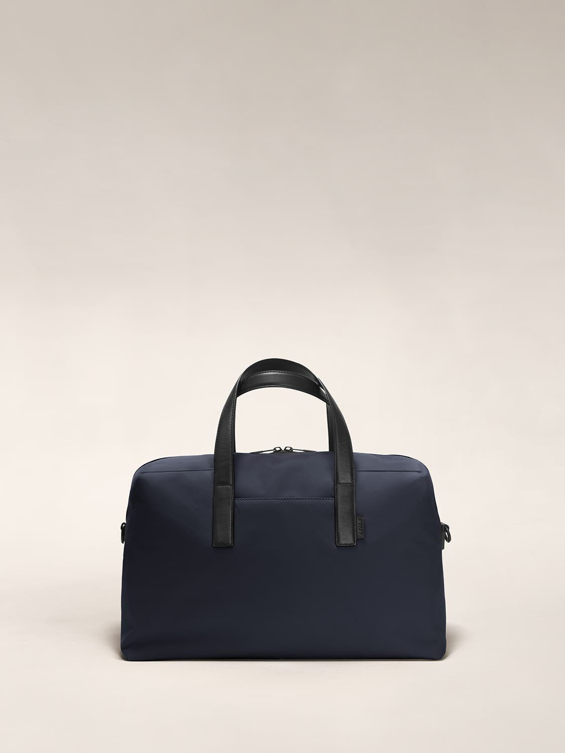 Front of a navy duffle bag with raised straps.