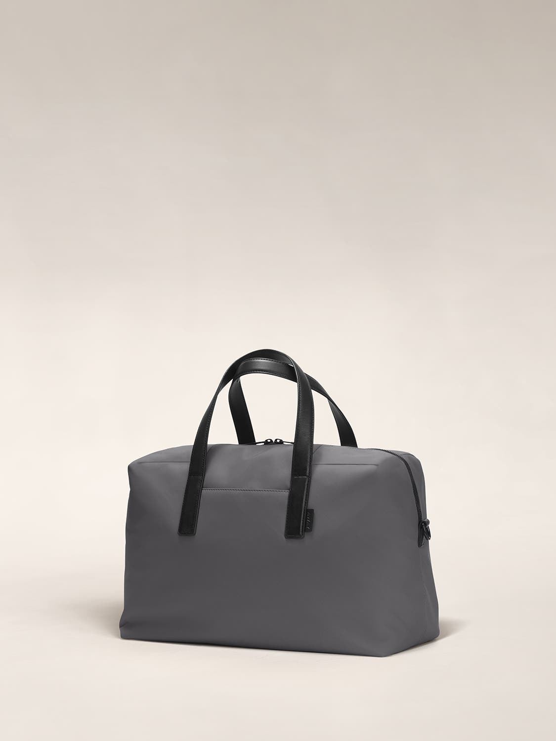 Angled view of a gray duffle bag with crossed straps.