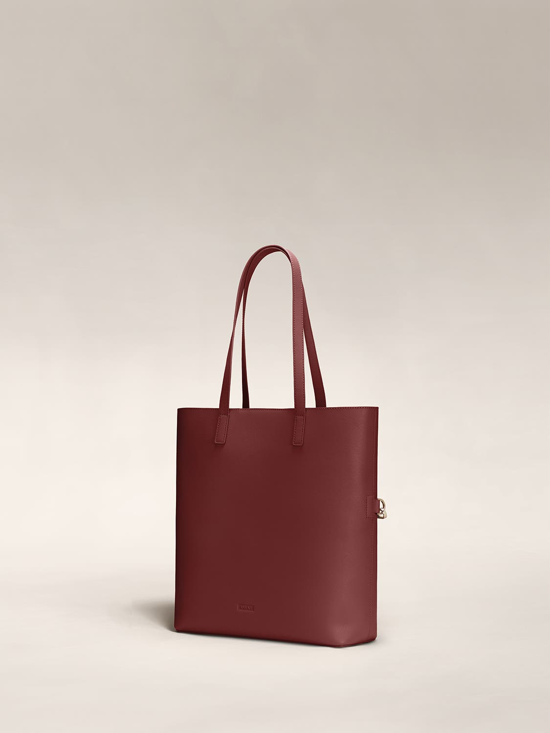 Angled view of a ruby red leather tote travel bag in leather.