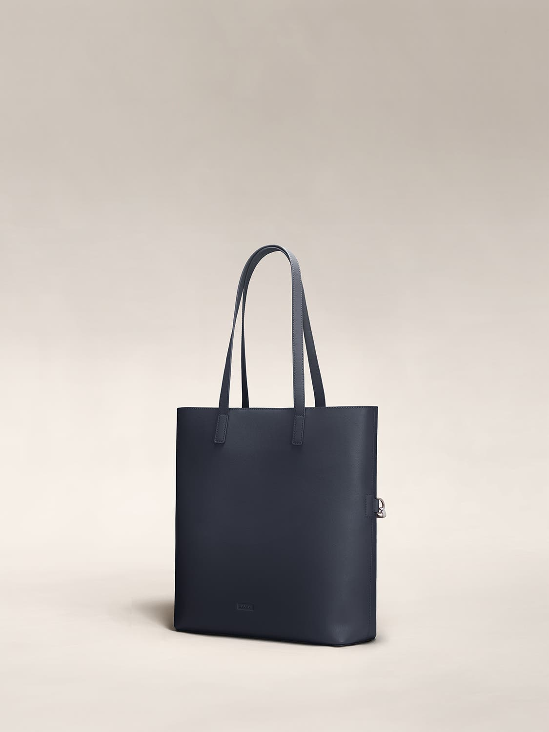 Angled view of a navy leather tote travel bag in leather.
