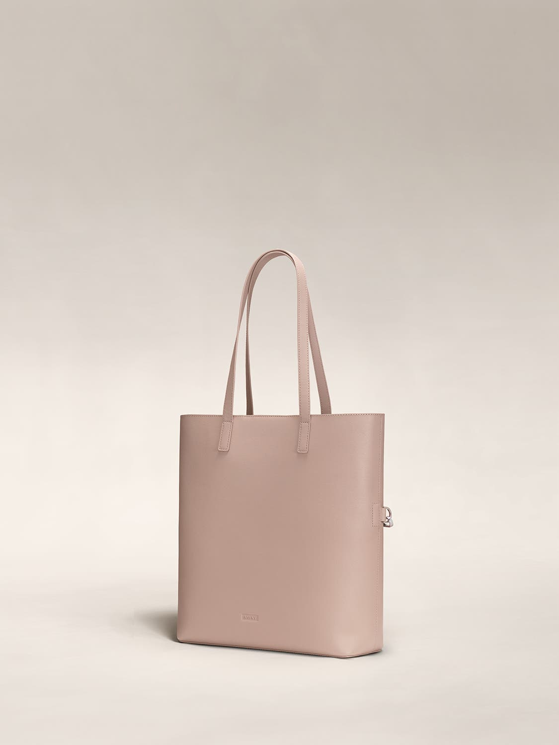 Angled view of a rose pink leather tote travel bag in leather.