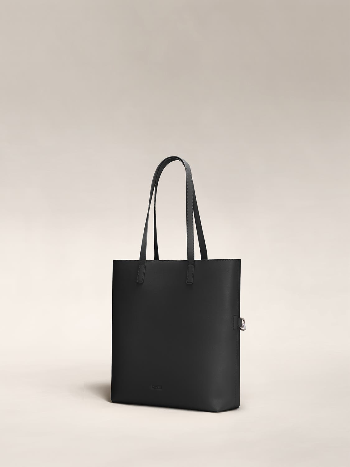 Angled view of a black leather tote travel bag in leather.