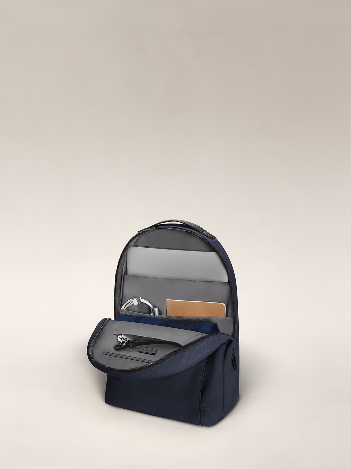 Navy daypack with organized pockets showing a laptop, notebooks and headphone.