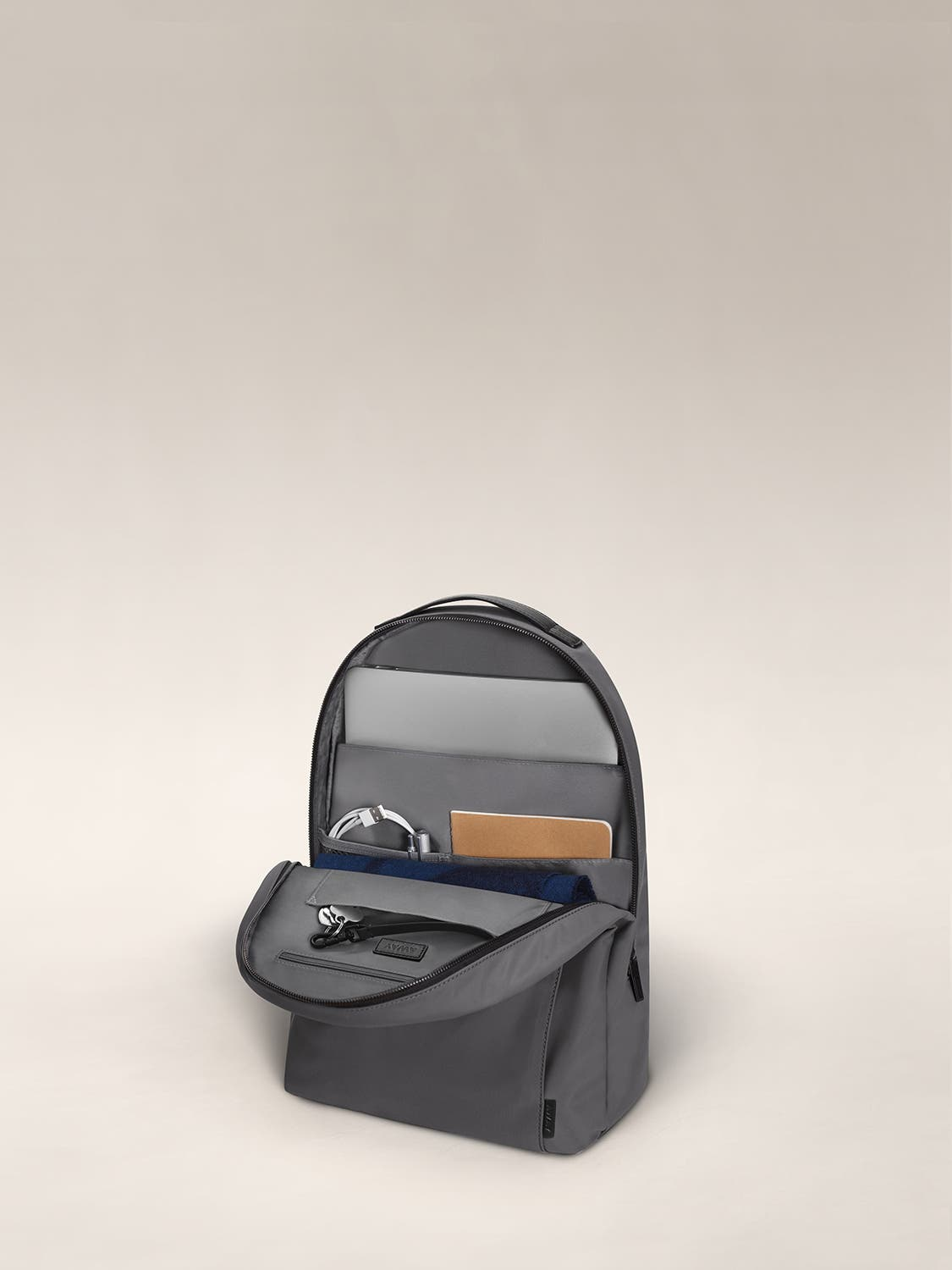 Gray daypack with organized pockets showing a laptop, notebooks and headphone.