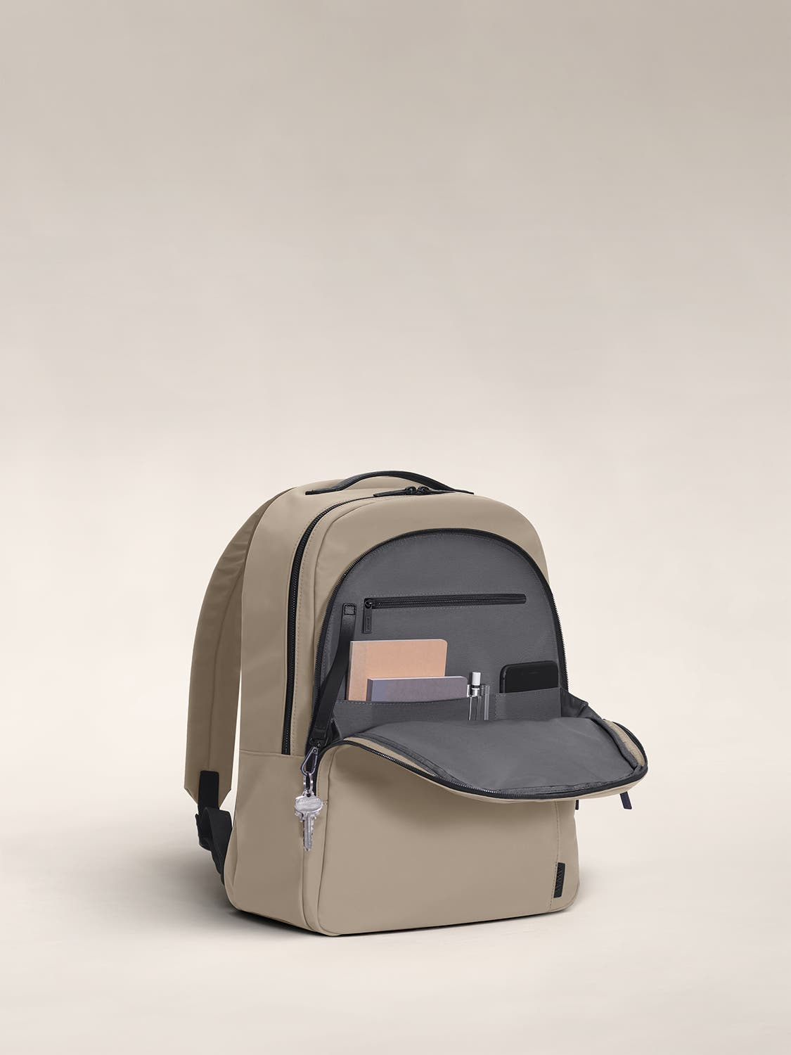 Open front flap of a sand backpack with organized pockets shown with notebooks.