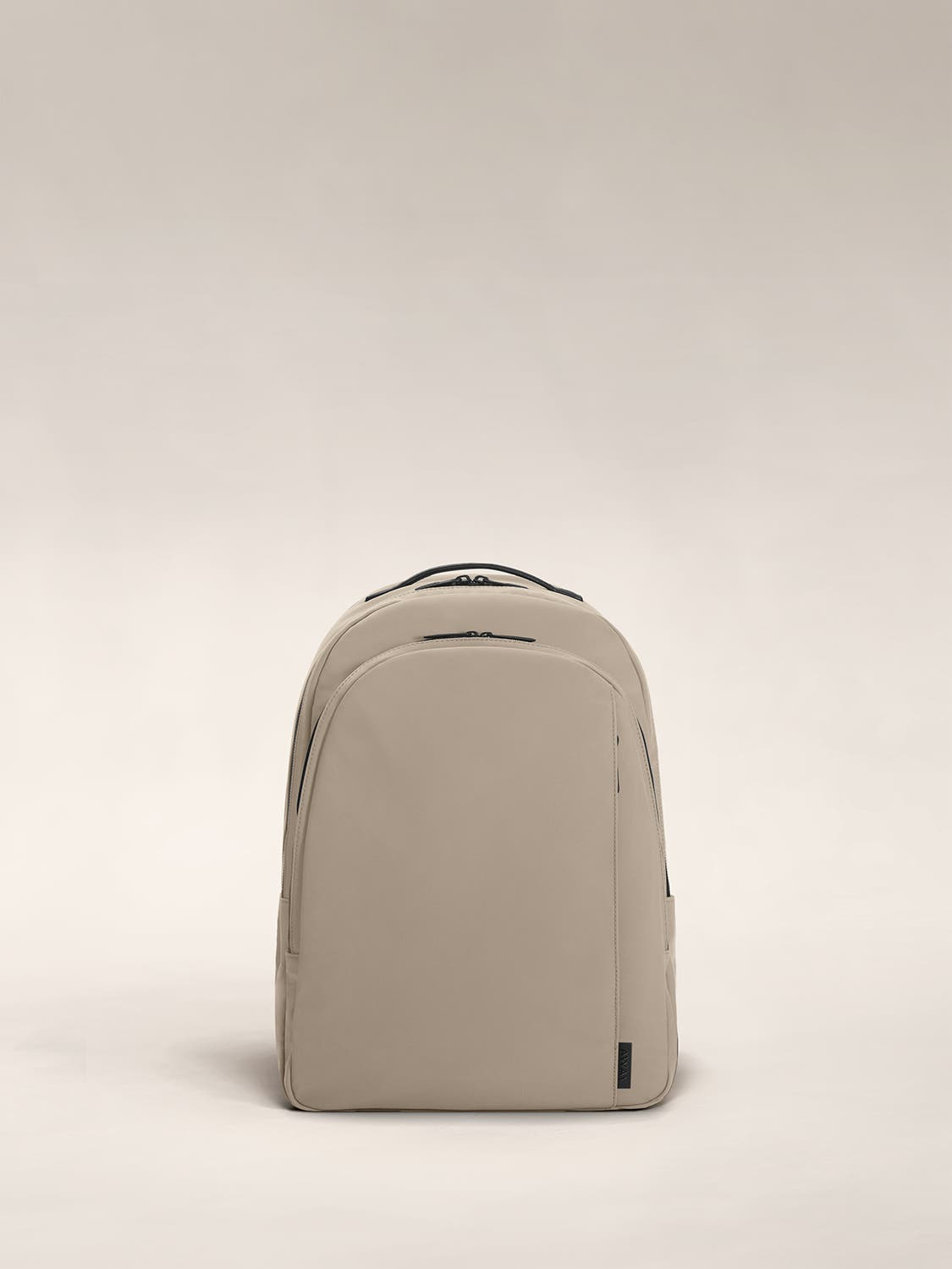Sand color backpack with one large zip compartment and one small one.