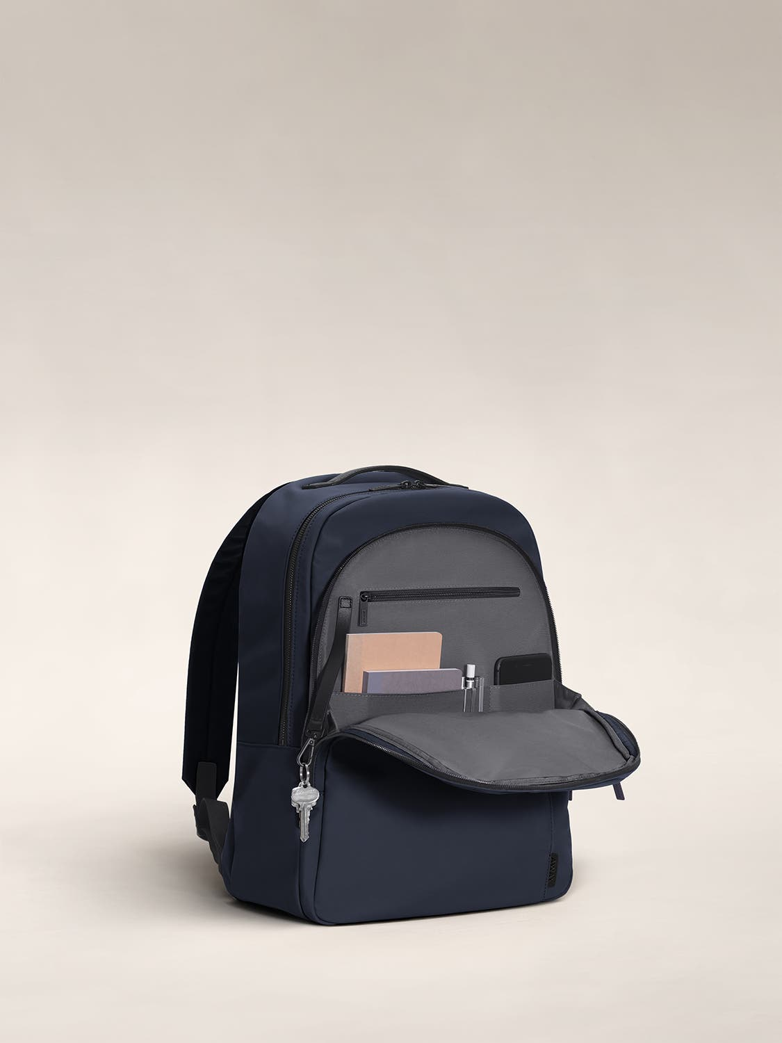Open front flap of a blue backpack with organized pockets shown with notebooks.
