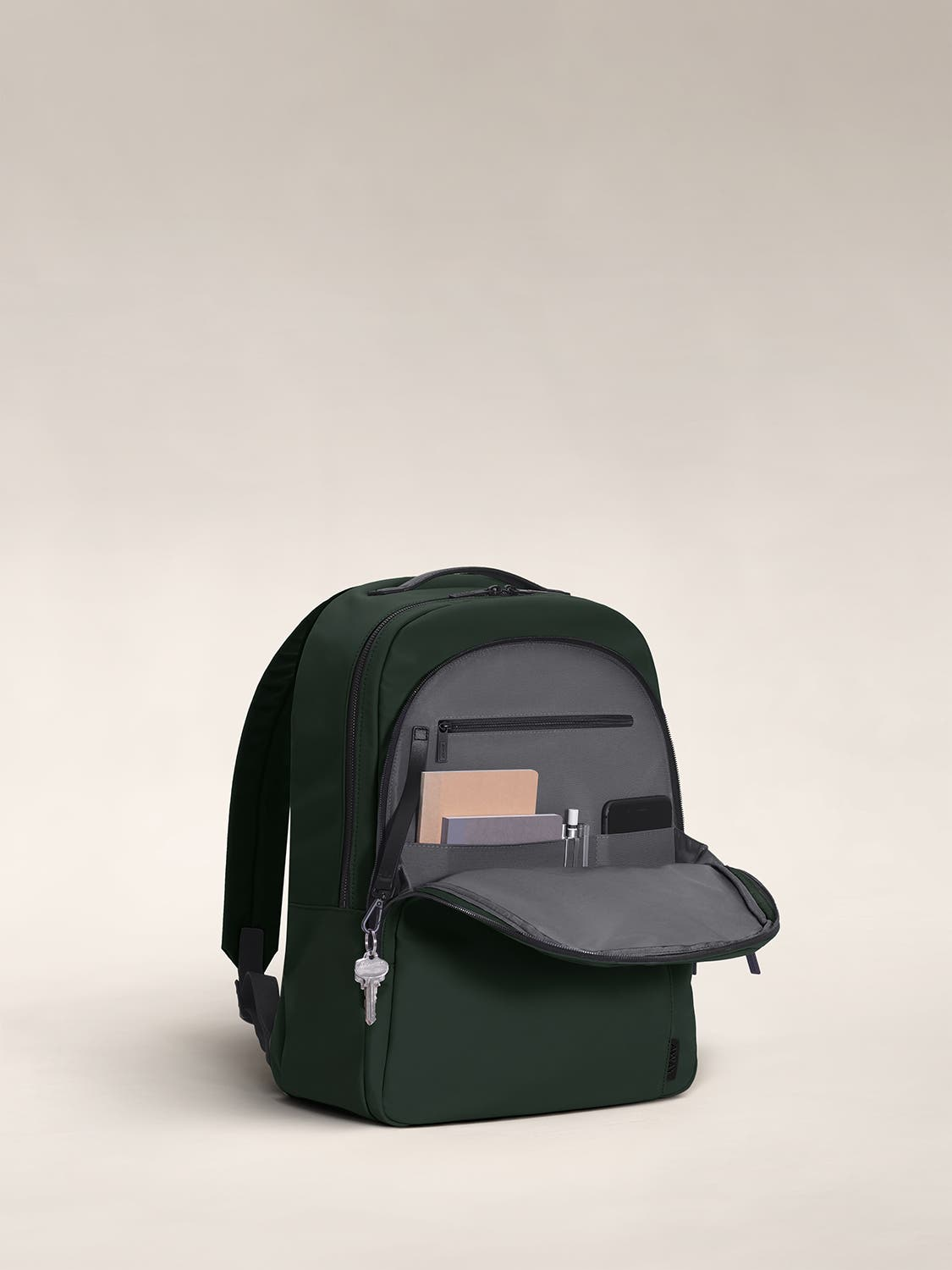 Open front flap of a green backpack with organized pockets shown with notebooks.