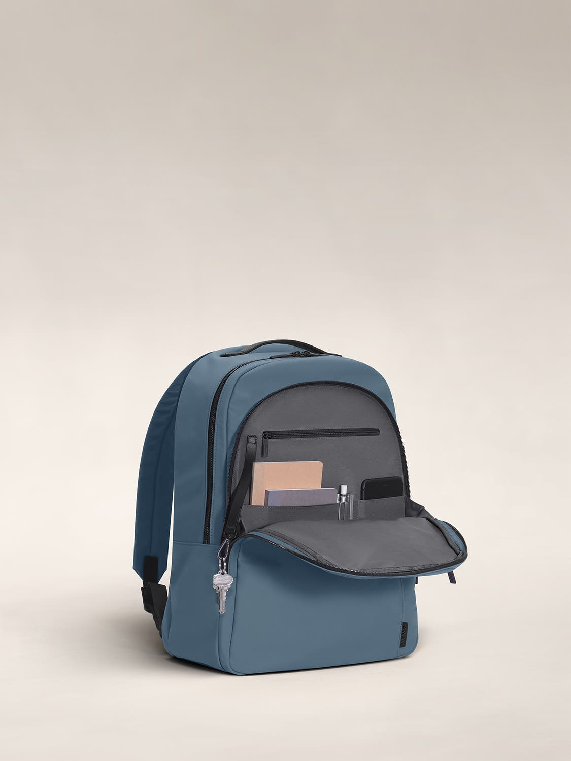 Open front flap of a coast blue backpack with organized pockets shown with notebooks.