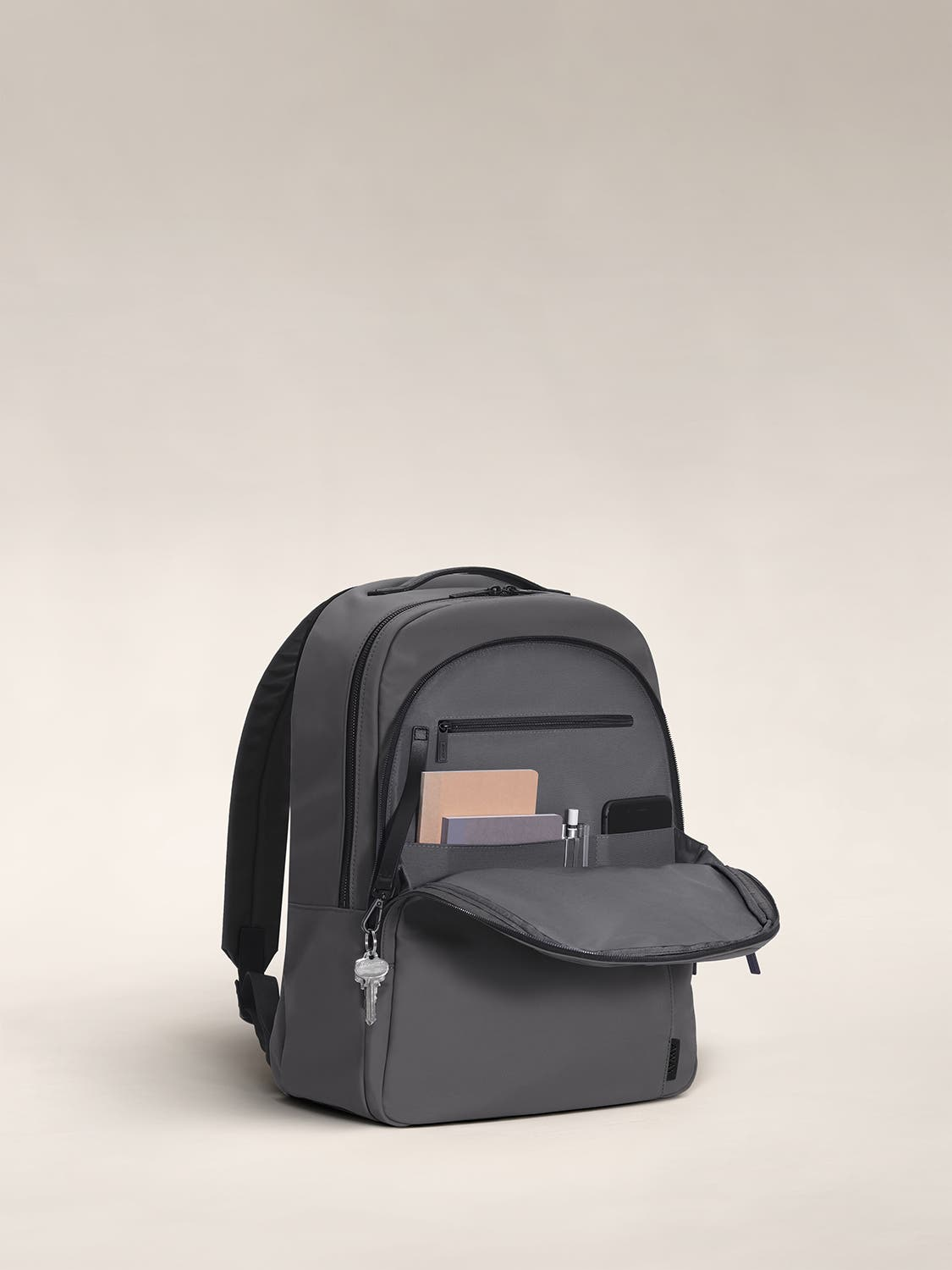 Open front flap of an asphalt backpack with organized pockets shown with notebooks.