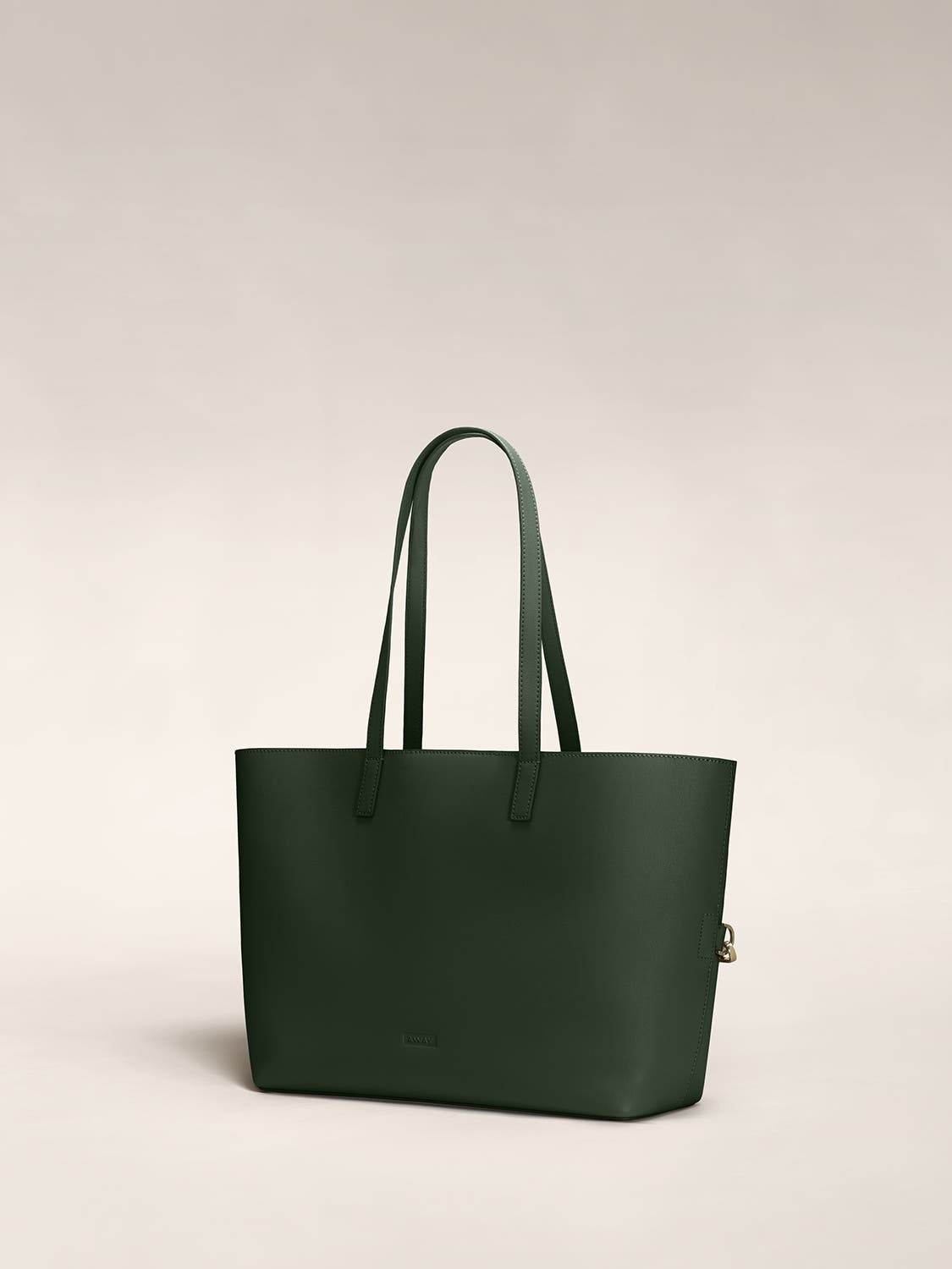 Angled view of a pine leather tote travel bag in leather.