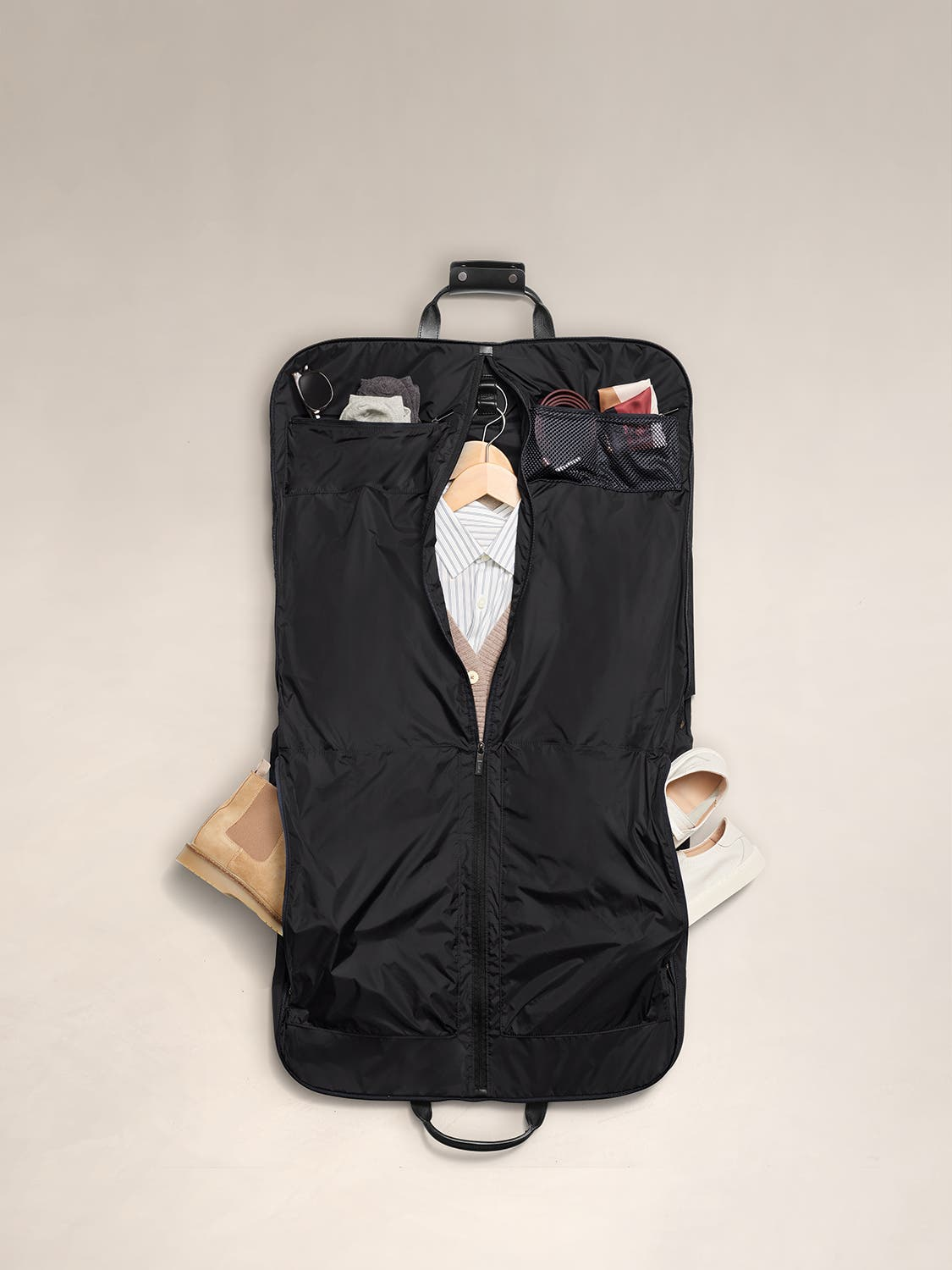 Black garment bag flat view with leather trim handles and shirt shown organized inside.