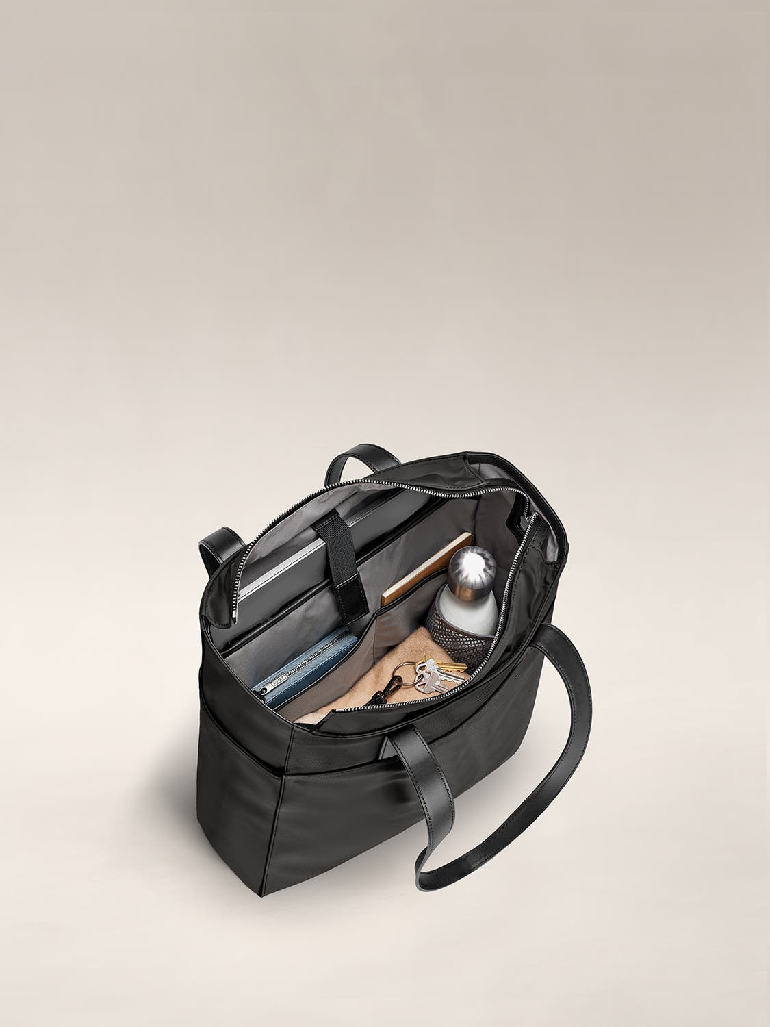 Fully packed and organized internal view of a black tote shoulder bag.