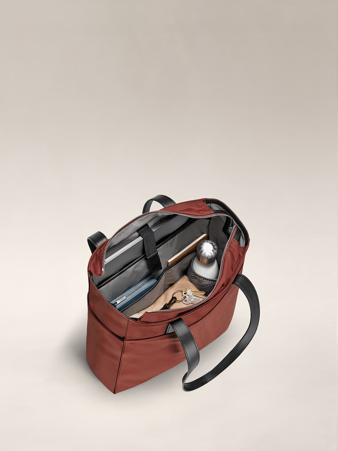 Fully packed and organized internal view of a brick red tote shoulder bag.