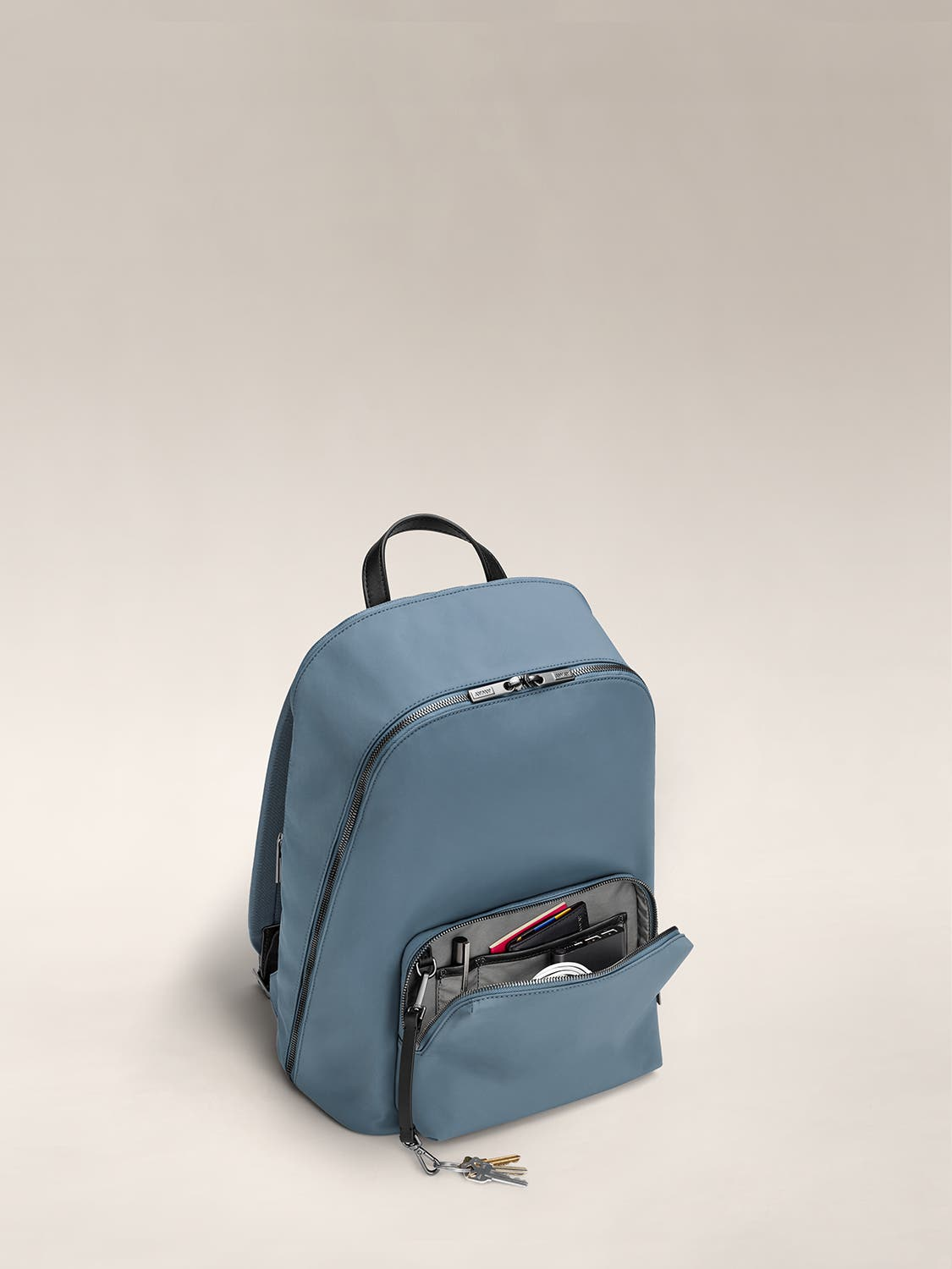 Small front pocket of a coast blue backpack unzipped and showing various accessories and documents organized inside.