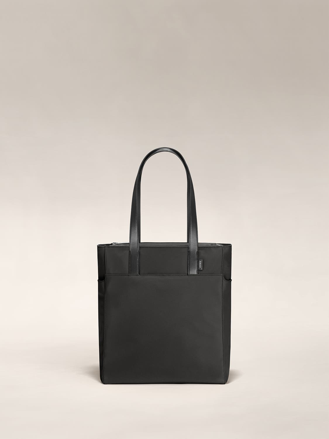 A black zip tote with leather handles raised.