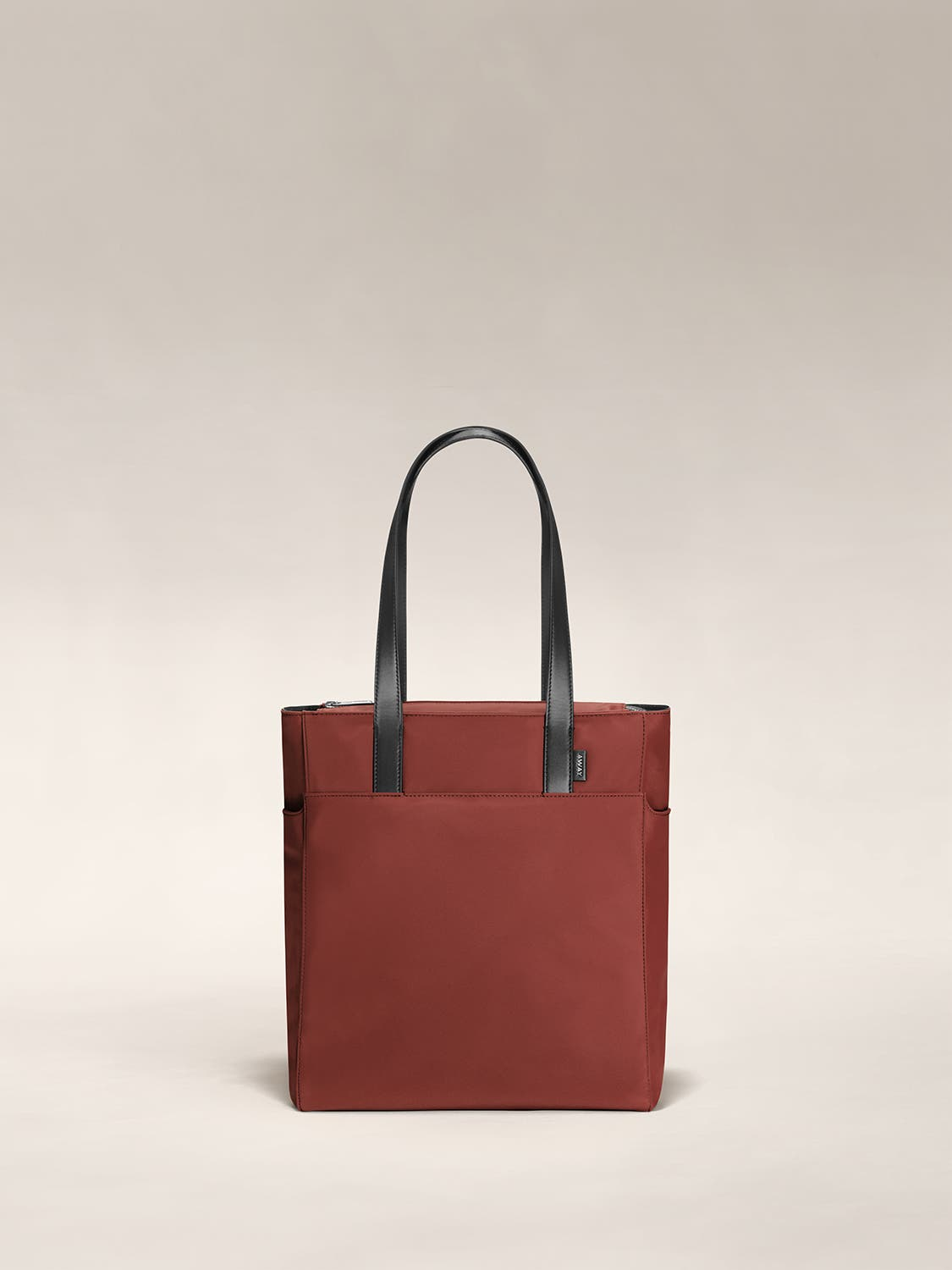 A brick red zip tote with leather handles raised.
