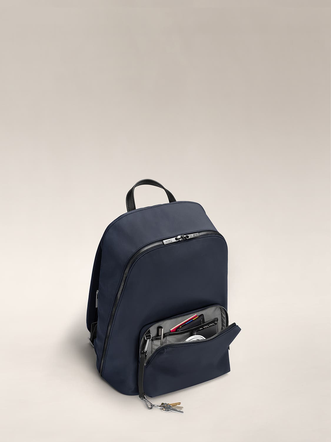 Small front pocket of a navy blue backpack unzipped and showing various accessories and documents organized inside.