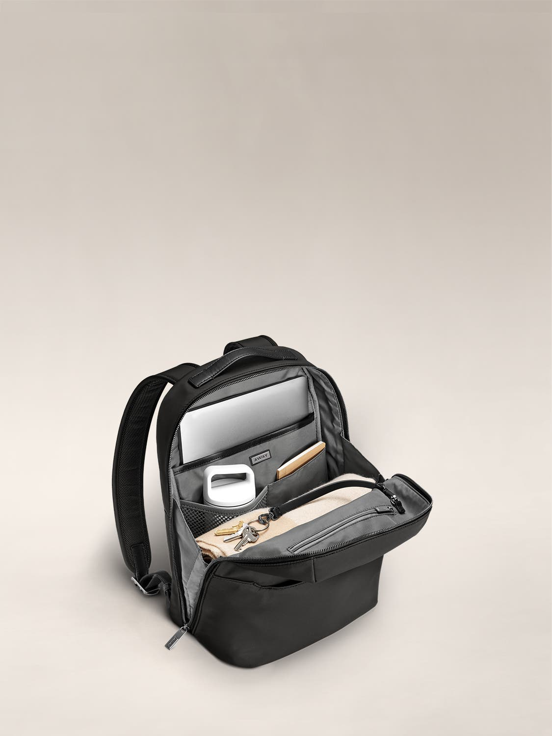 Inside view of a small backpack in black with internal pockets organized with various accessories.