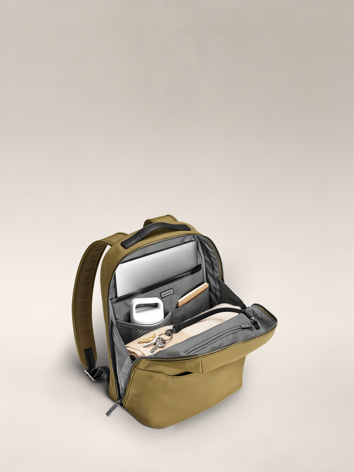 Inside view of a small backpack in moss green with internal pockets organized with various accessories.