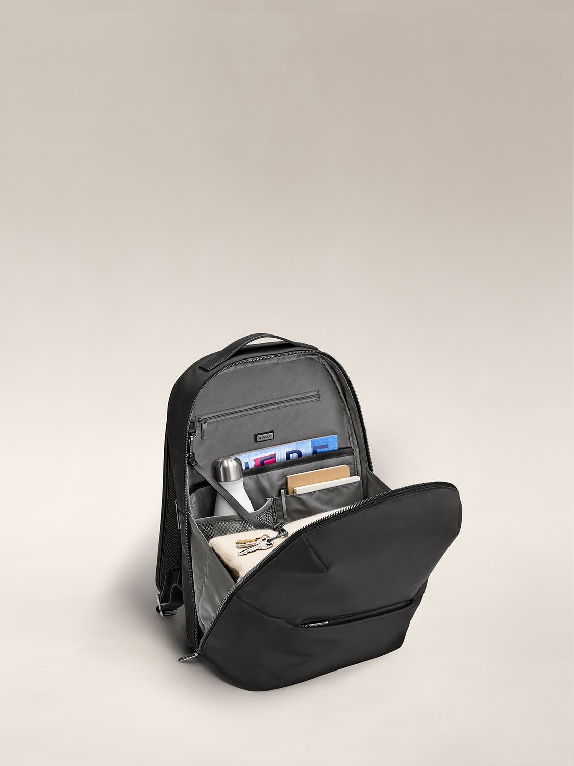 Inside view of black backpack with grey lining showing travel accessories packed and organized in the various pockets.