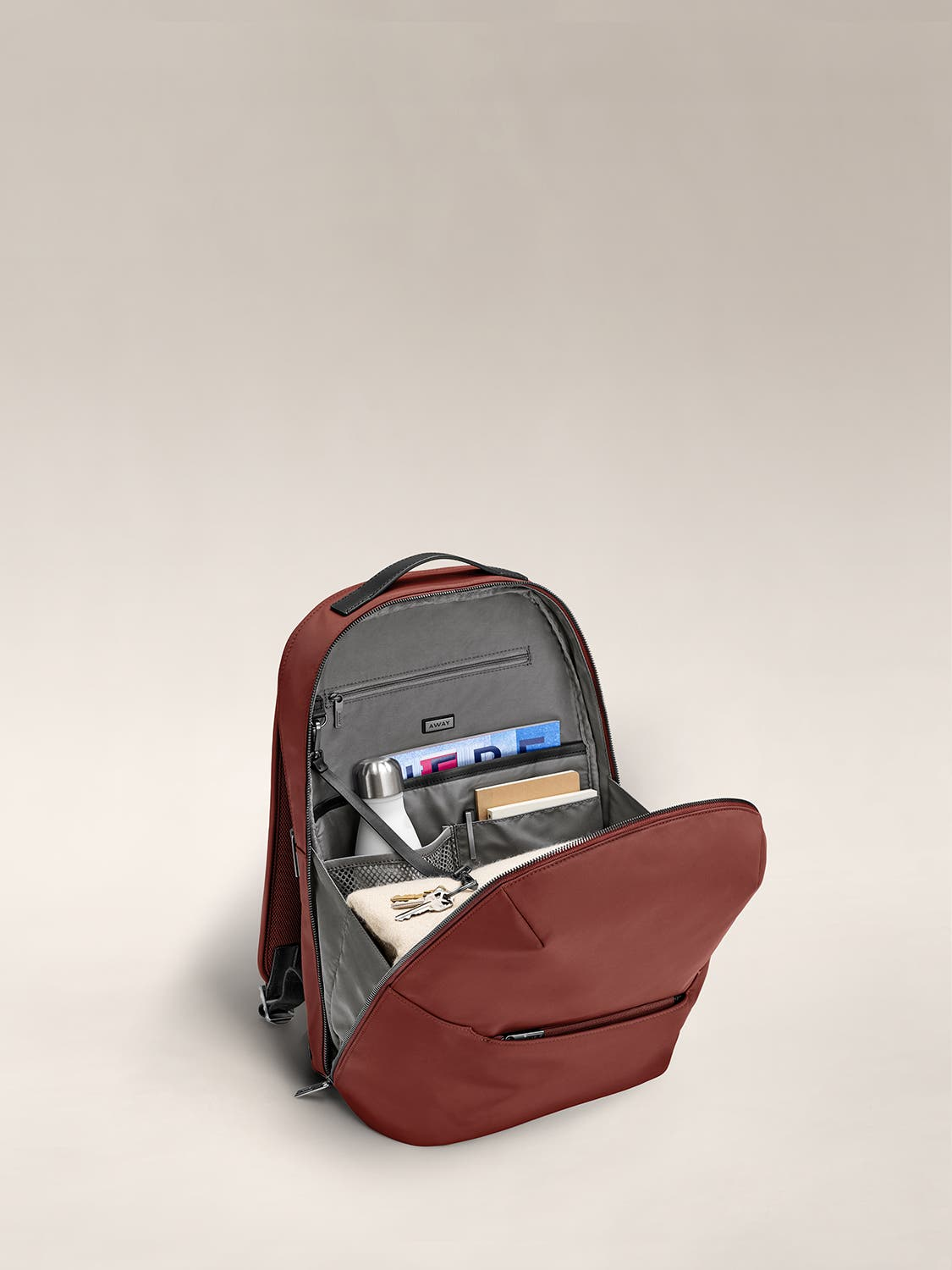 Inside view of brick red backpack with grey lining showing travel accessories packed and organized in the various pockets.