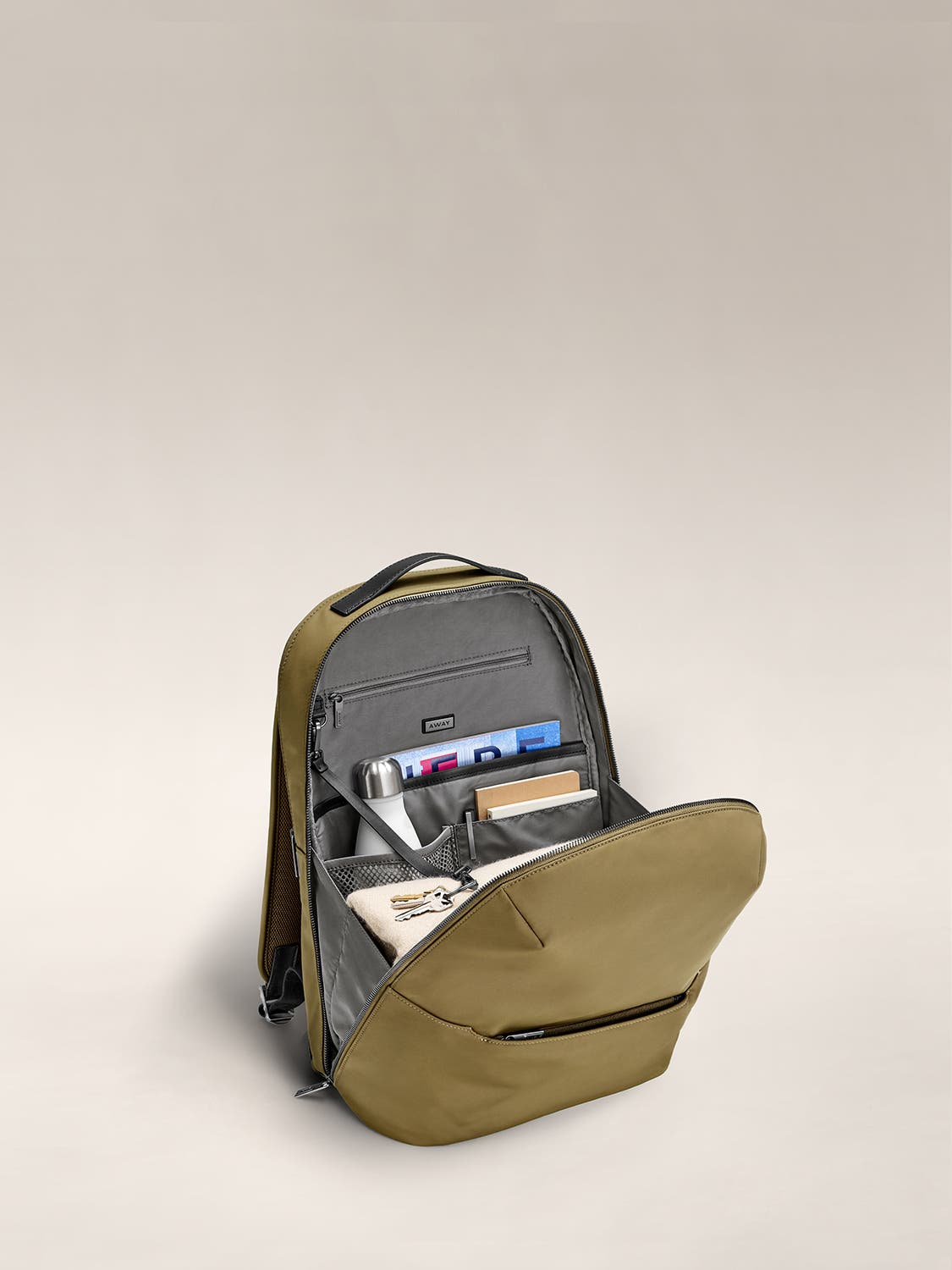 Inside view of moss green backpack with grey lining showing travel accessories packed and organized in the various pockets.