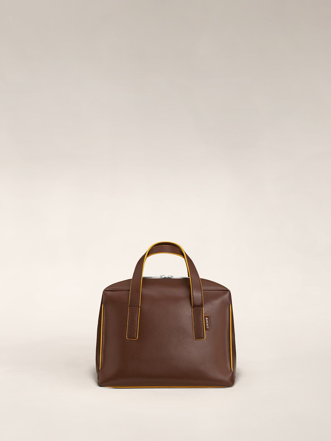 Chestnut mini travel bag with handle straps raised vertically.
