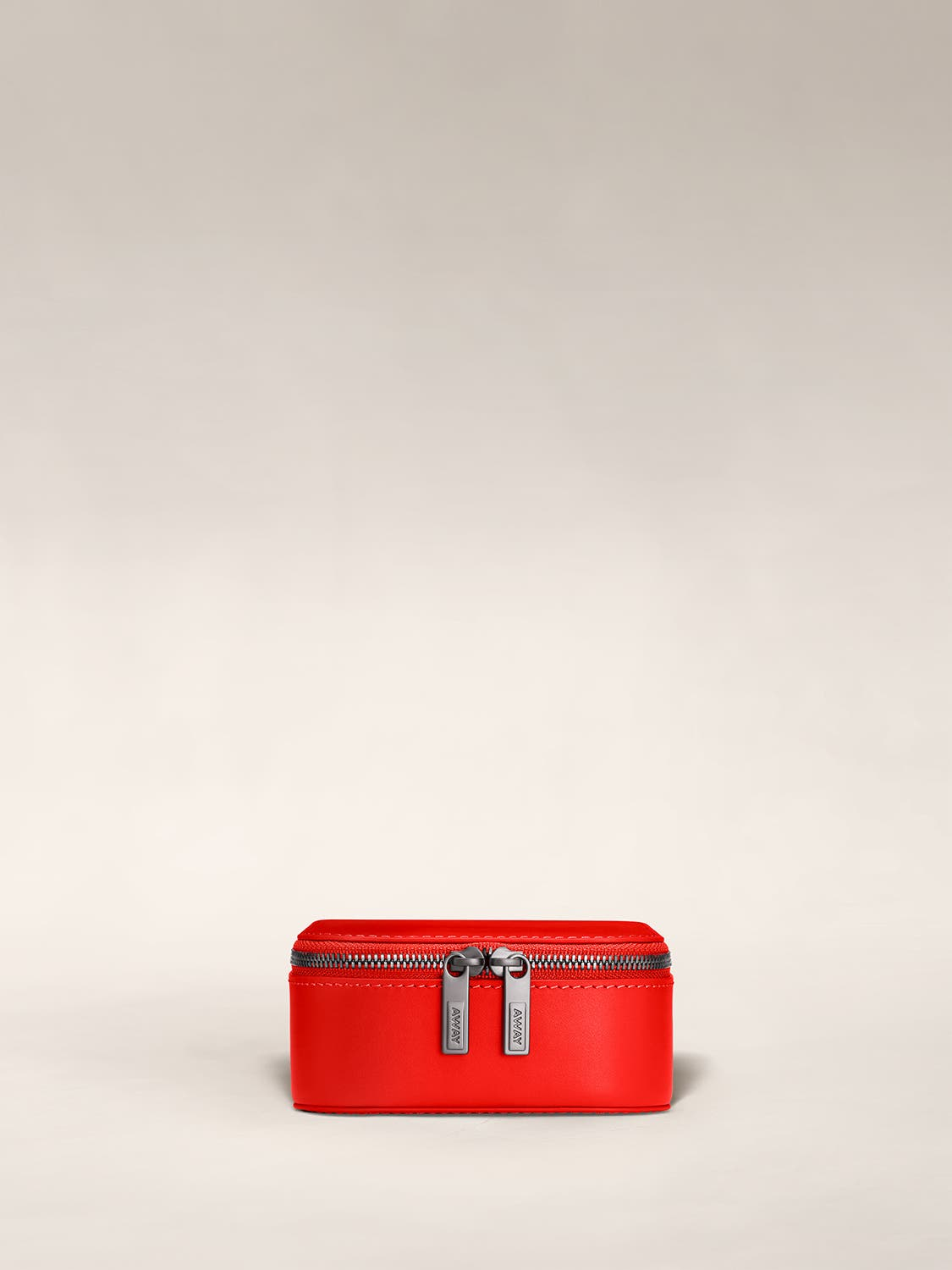 Front view of a cherry jewelry box zipped with Away logo on zip.