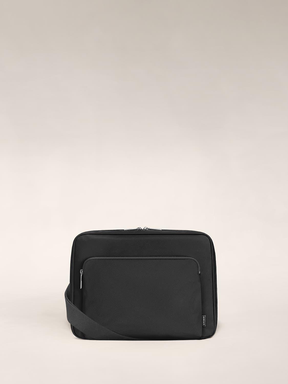 A black messenger bag with a main pocket and a small wraparound pocket.