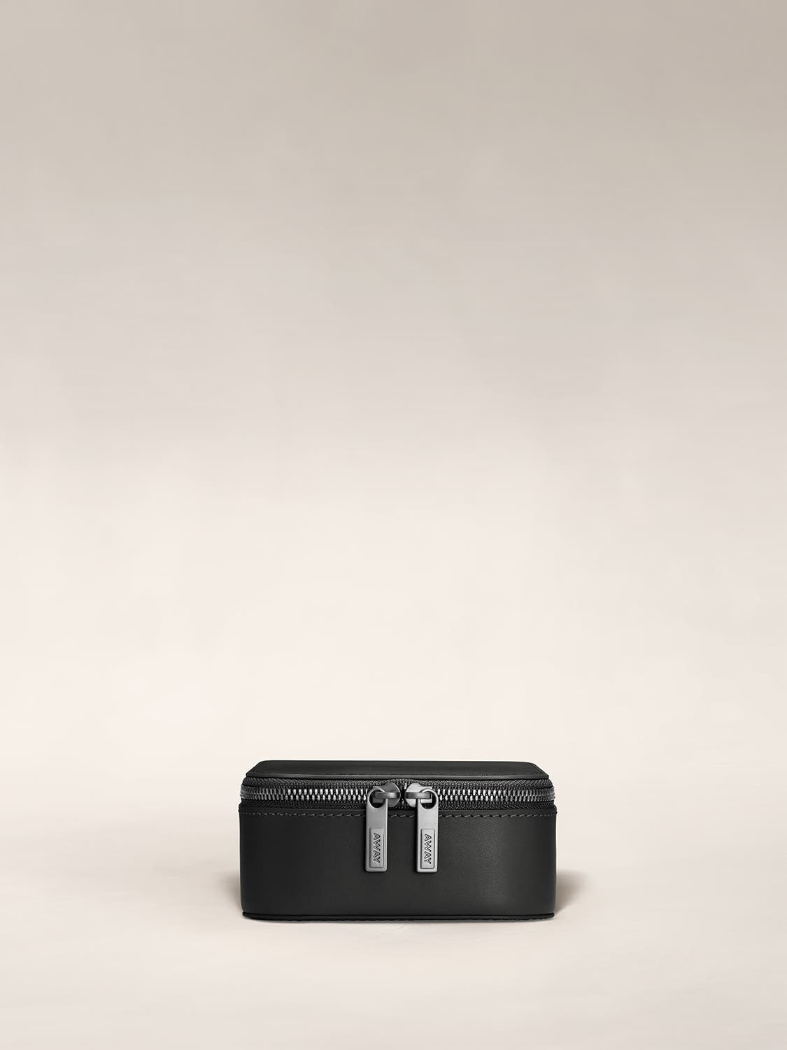 Front view of a black jewelry box zipped with Away logo on zip.
