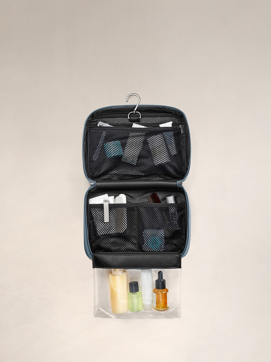 An internal view of a coast toiletry bag packed with travel accessories within mesh pockets.